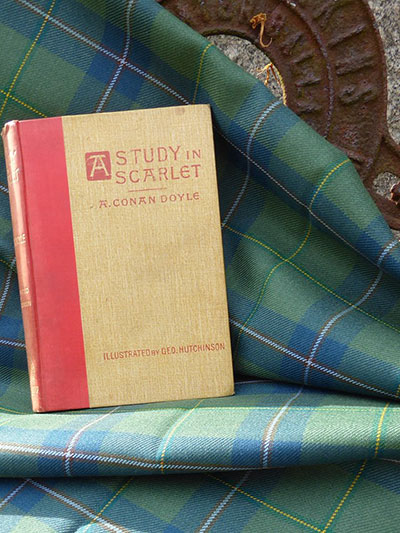 Sherlock Holmes book Study in Scarlet next to Sherlock Holmes Tartan