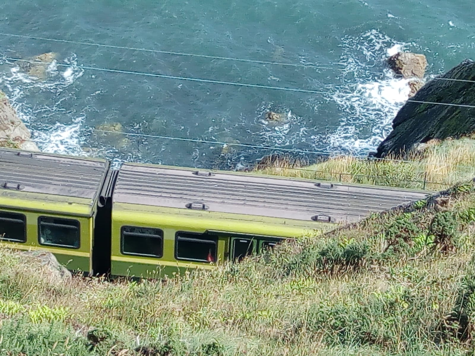The DART electric train runs along the sea at the bottom of the cliffs.