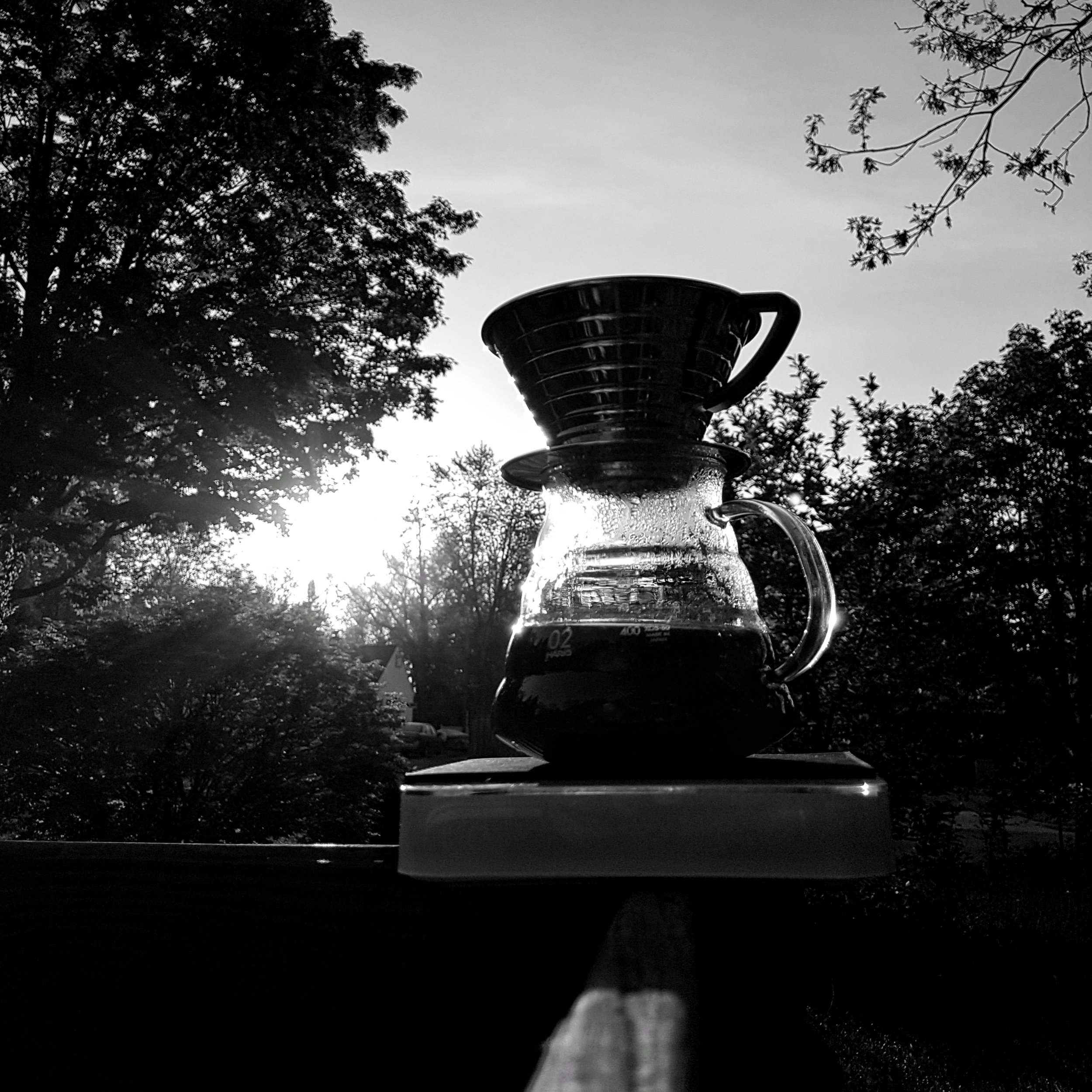 A Kalita Wave coffee brewer on a scale on a fence against a sunrise