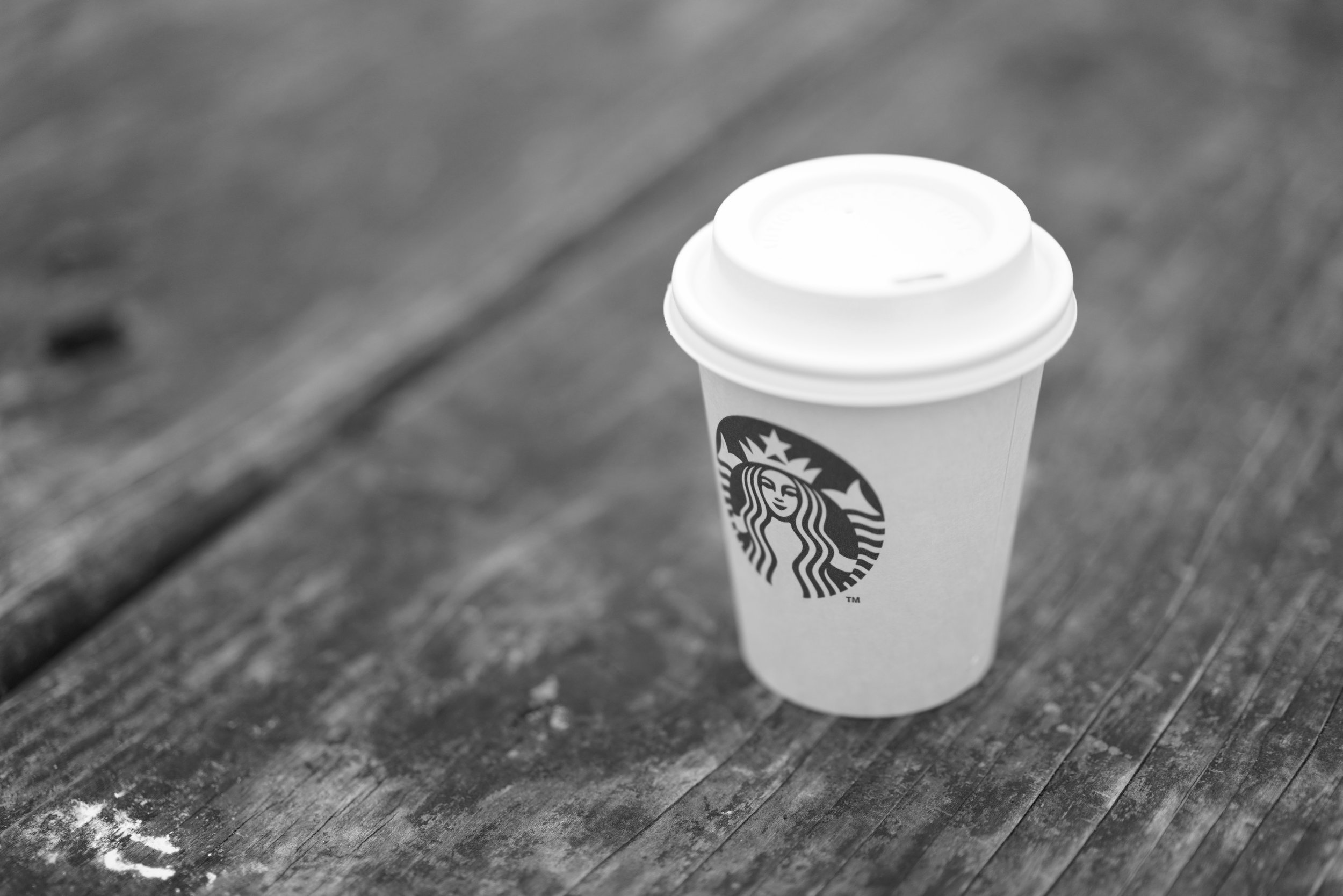 A white Starbucks takeaway cup sits on a wooden outdoor table