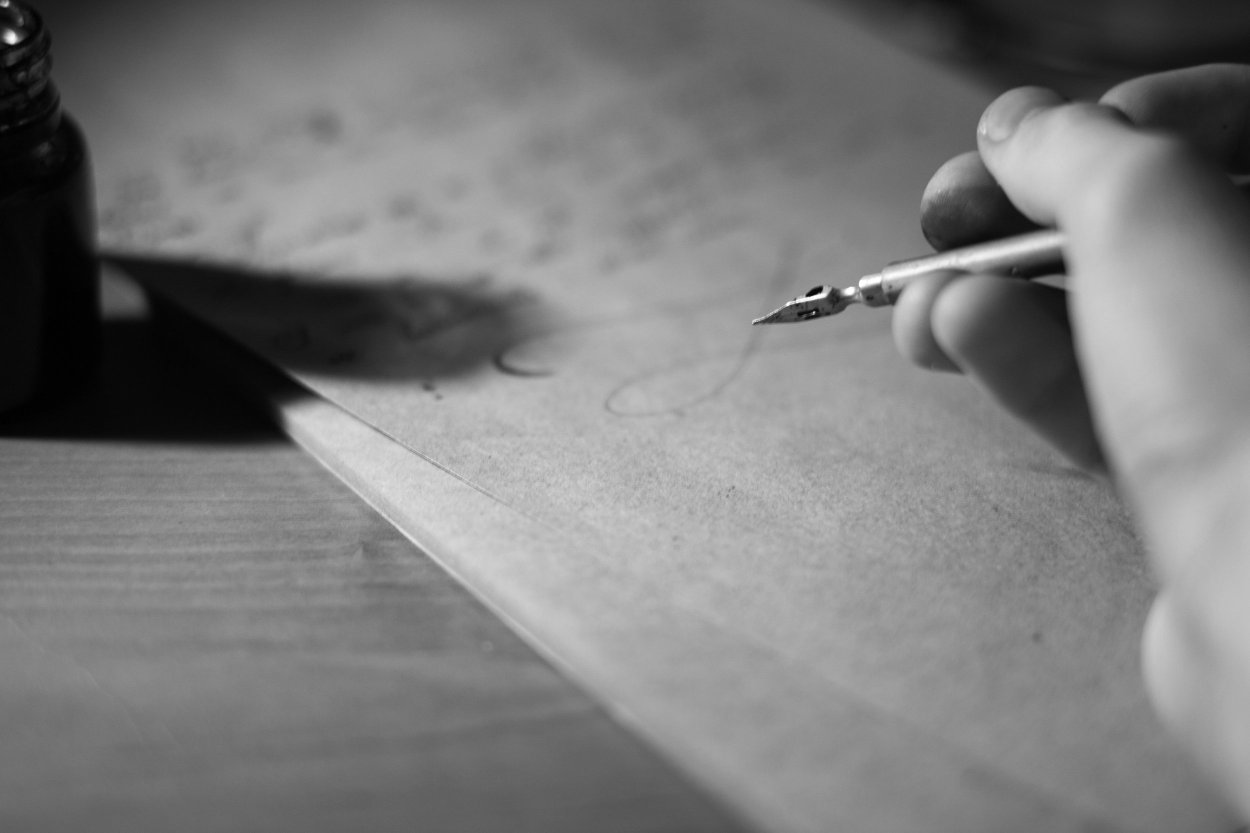 A hand writes using a quill
