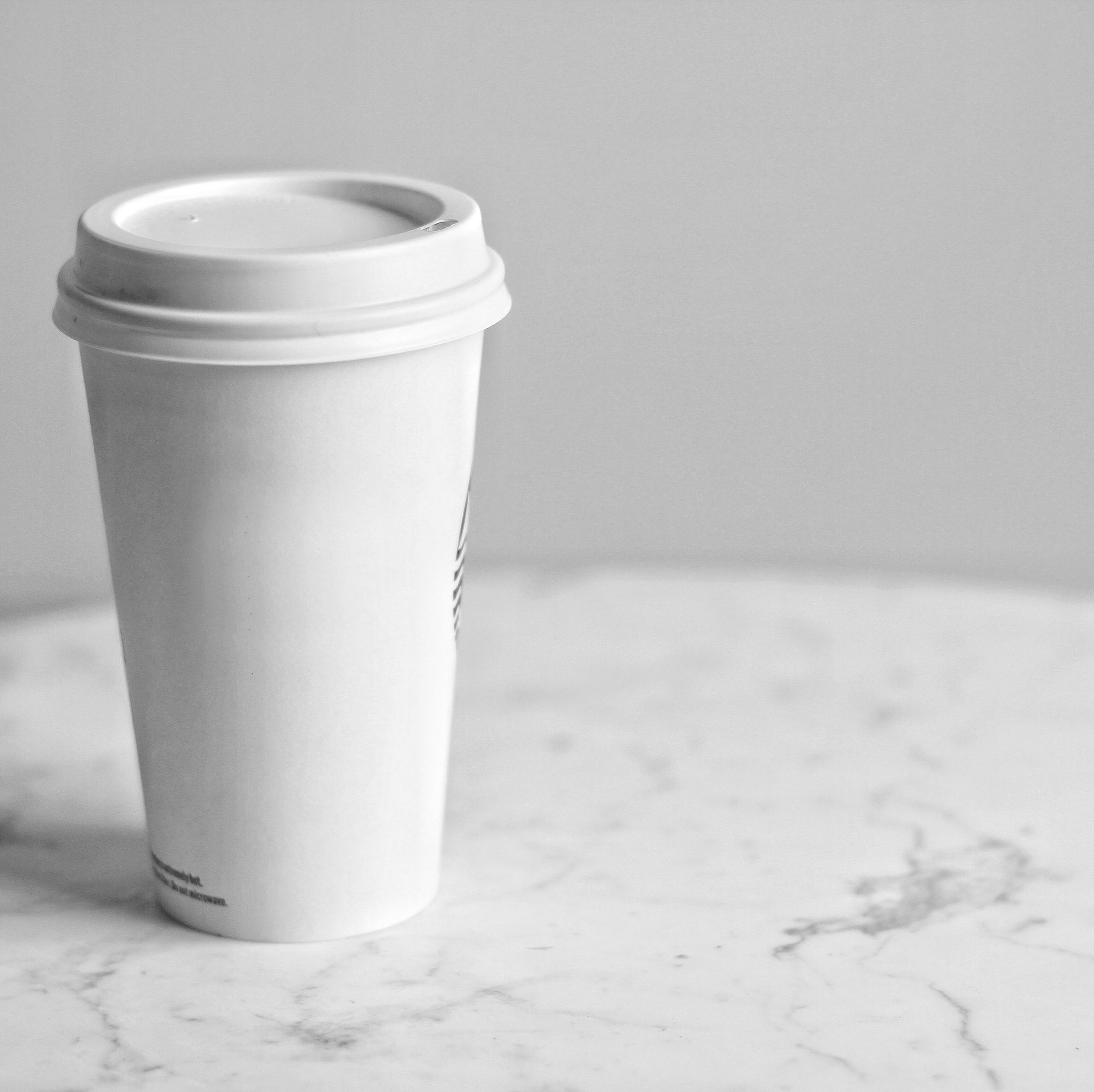A white single-use coffee cup sits on a marble table