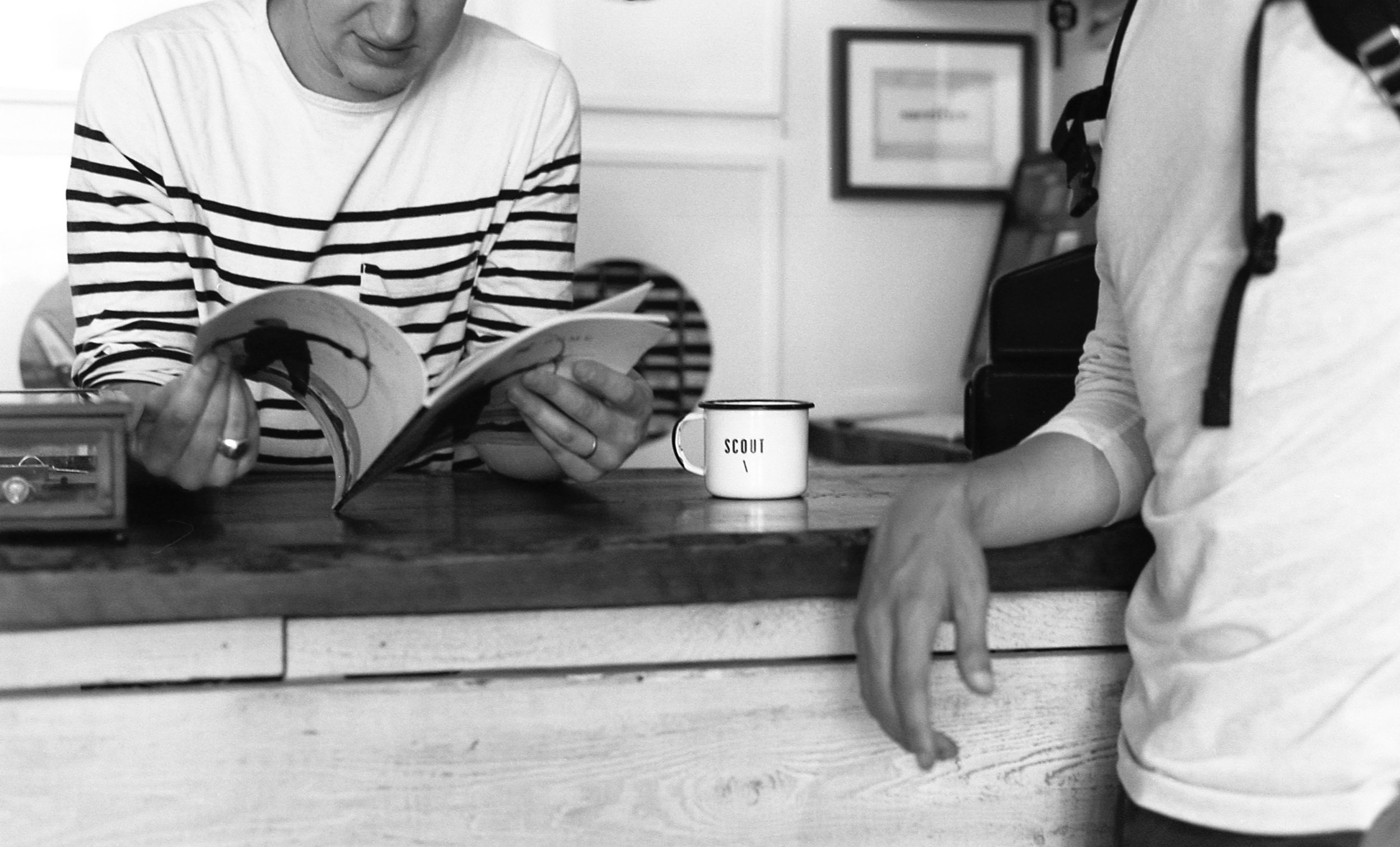 Two people lean on a counter, one reads a magazine