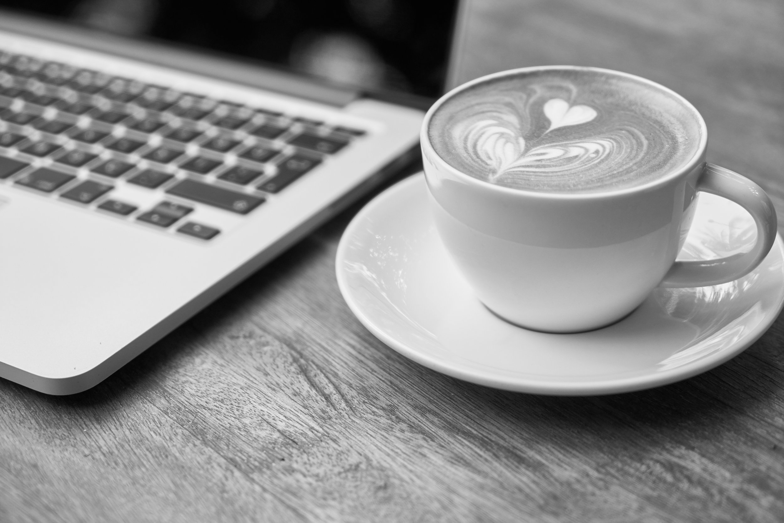 A latte and a Macbook sit on a wooden table