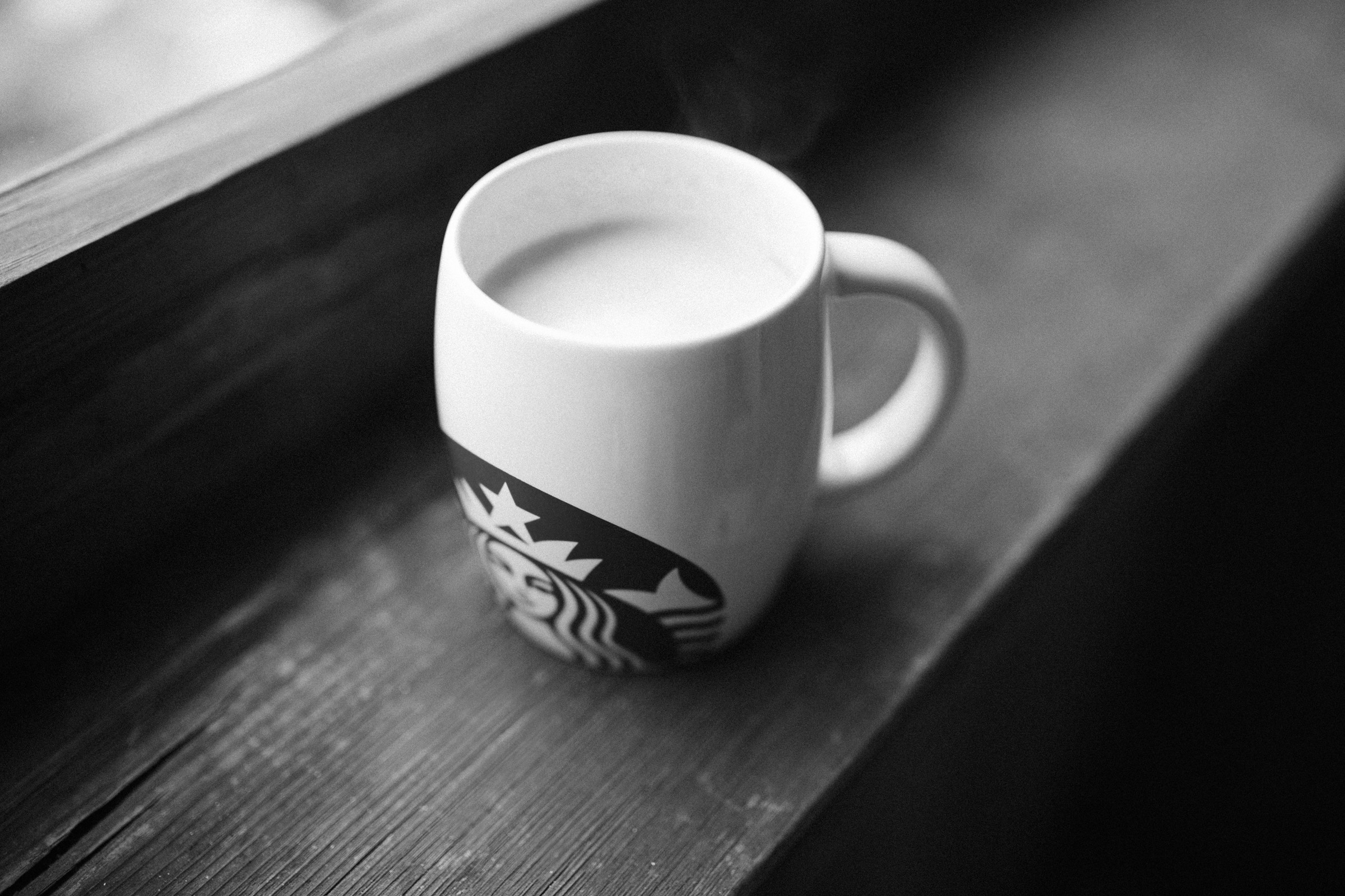 A mug of coffee on a wooden windowsill, with the Starbucks logo