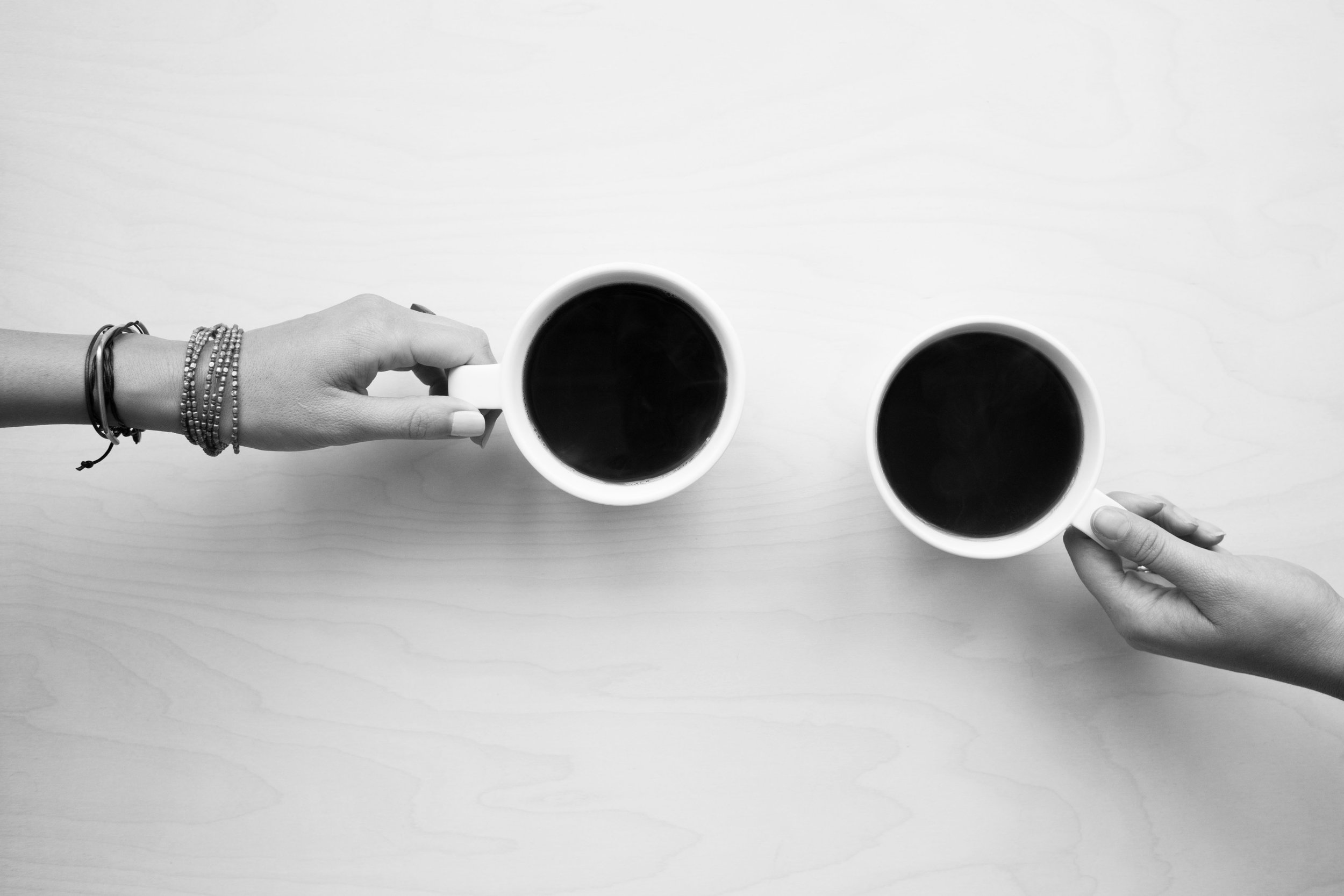 Two hands hold two cups of coffee from opposite sides of a table, seen from above