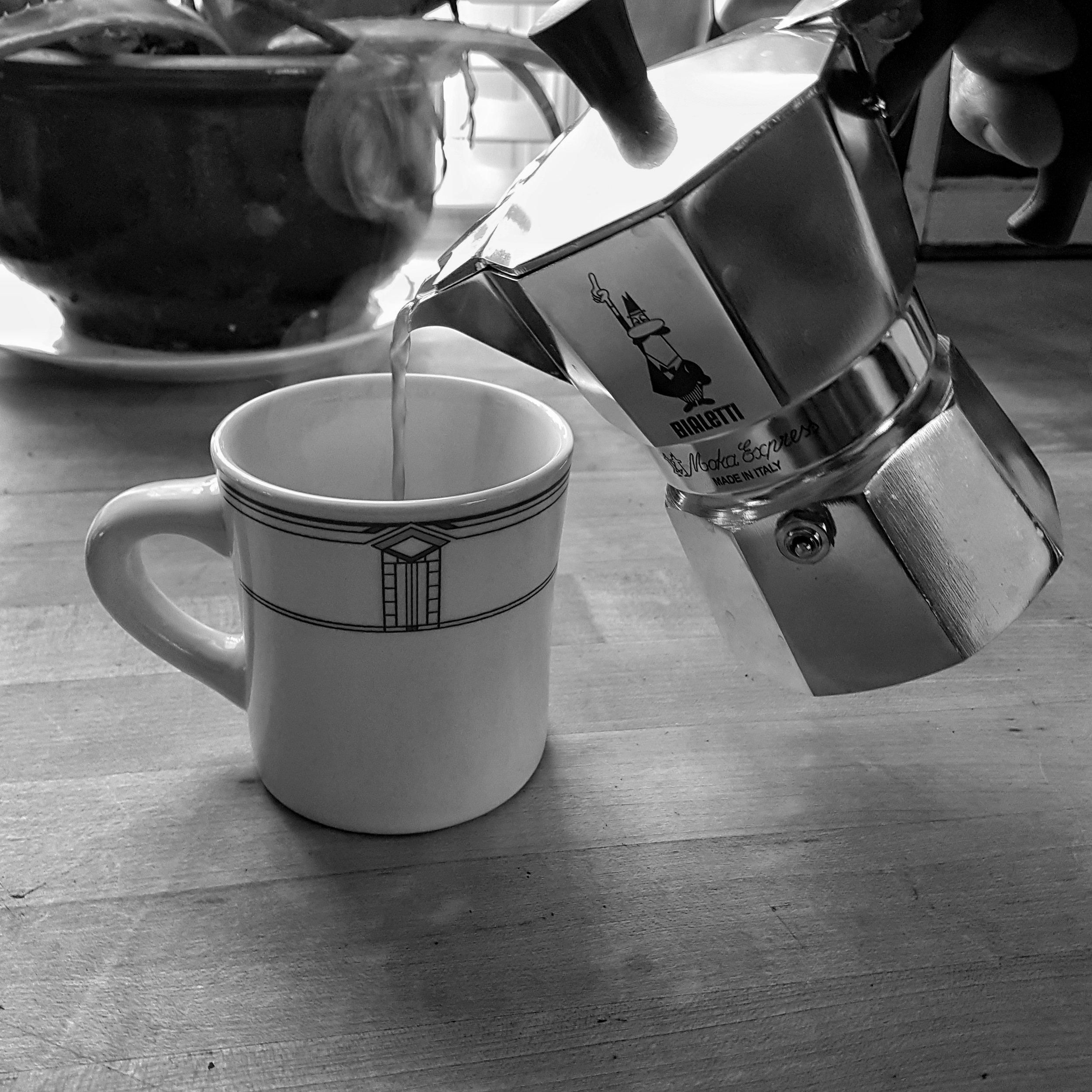 A Moka Pot pouring coffee into a cup on a table
