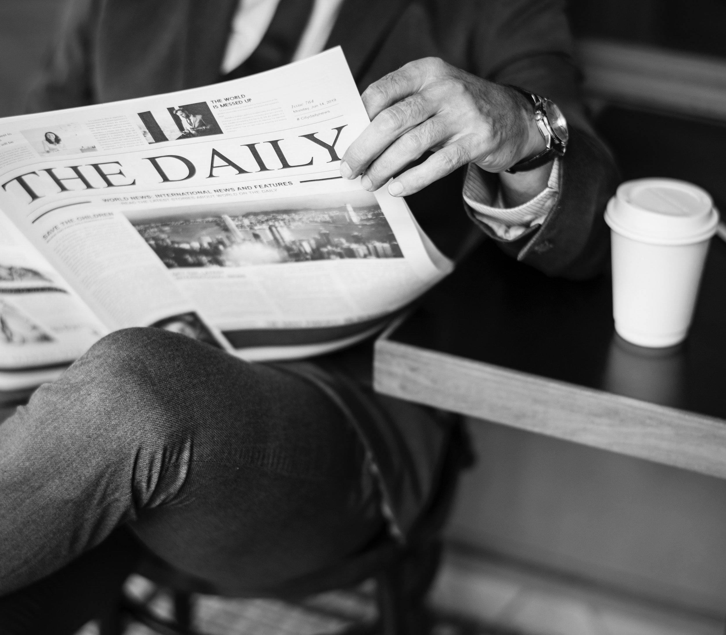 A person reads a newspaper while sitting on a bench with a paper coffee cup on a table beside them