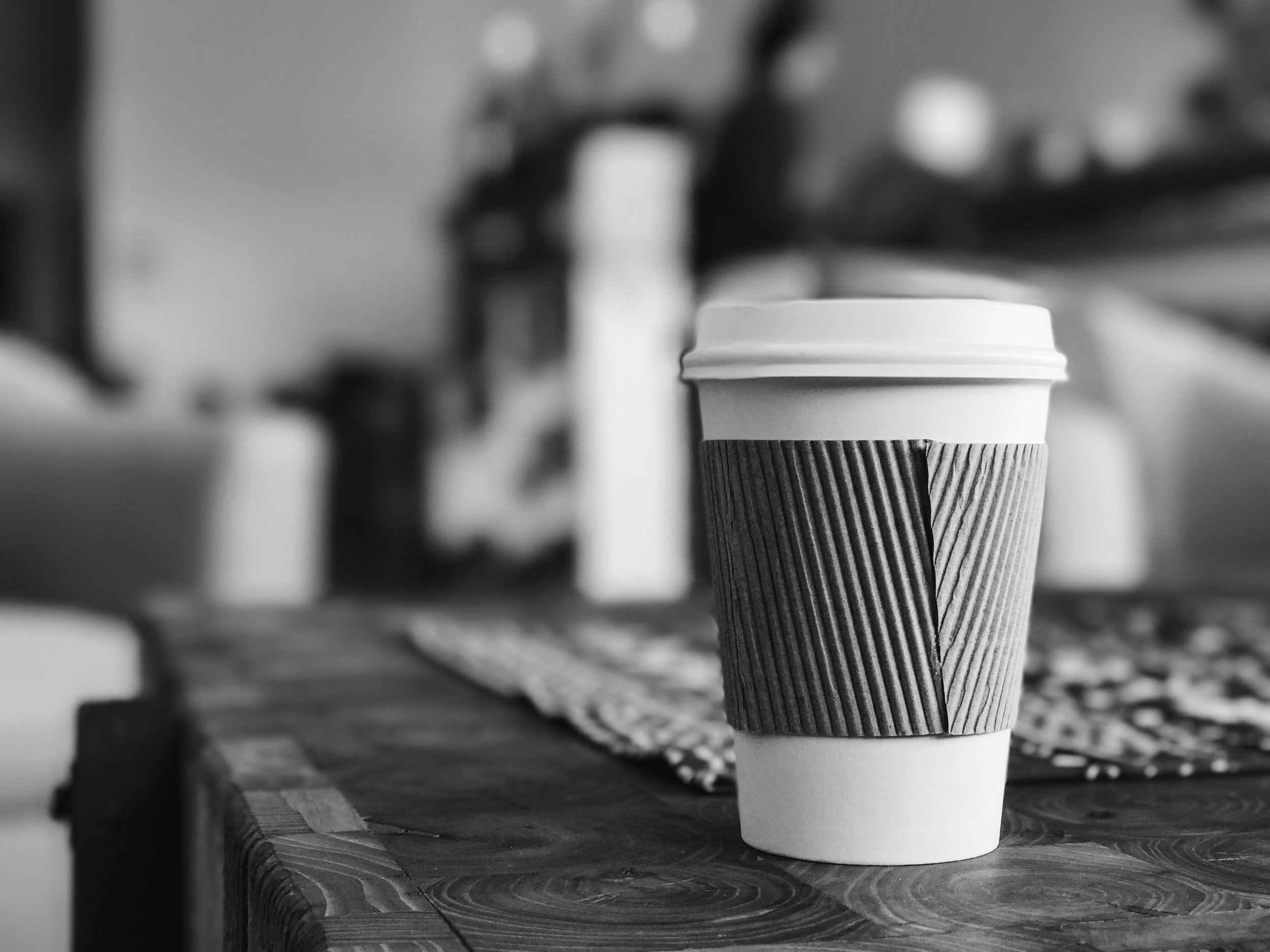 A disposable coffee cup sits on a table