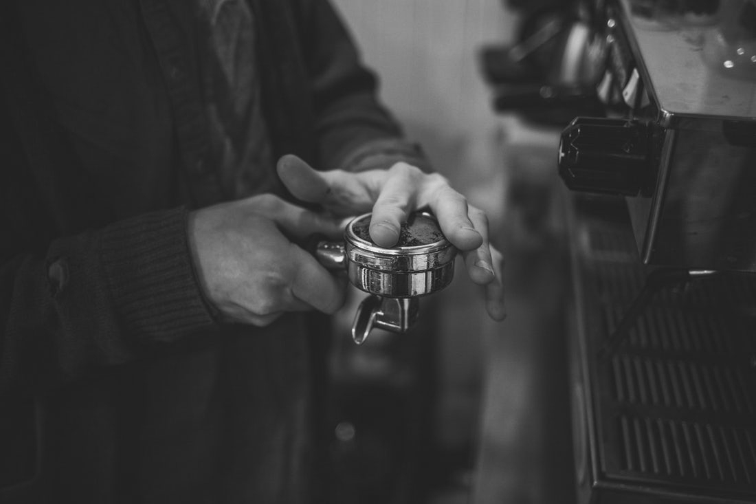 A barista smooths ground coffee in a portafilter with his finger.