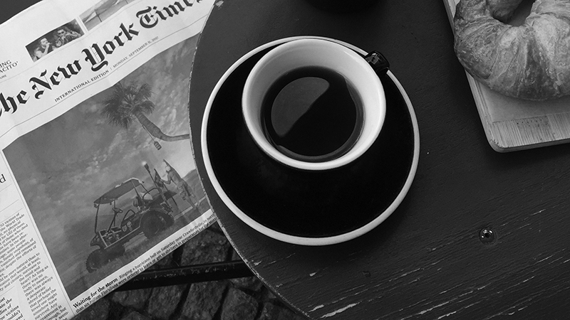 A coffee cup on a table next to a croissant and a newspaper