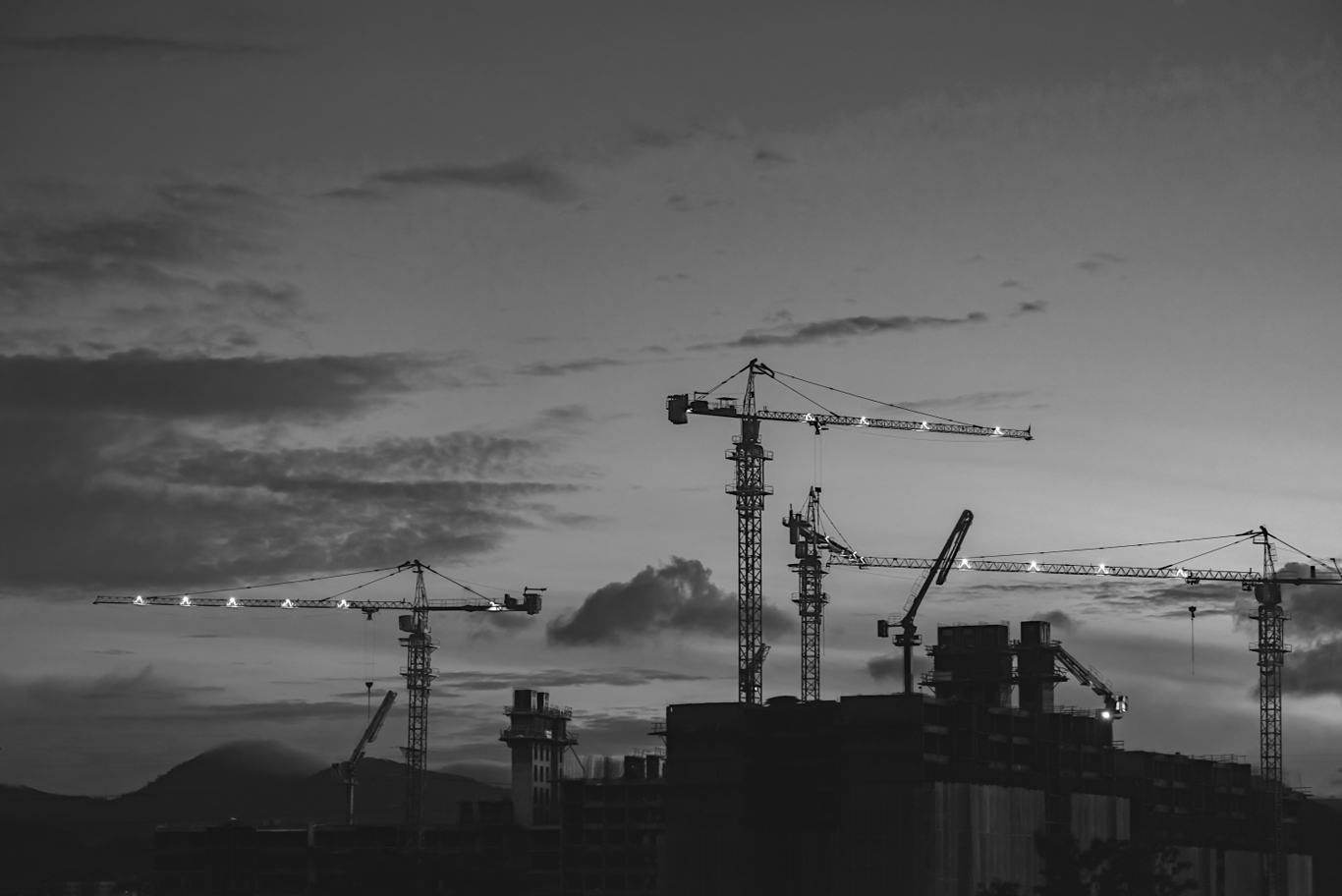 Cranes against a skyline at sunset