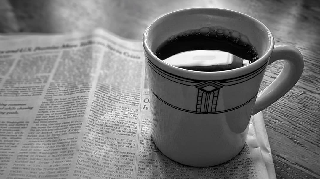 A diner mug sits atop a newspaper on a table