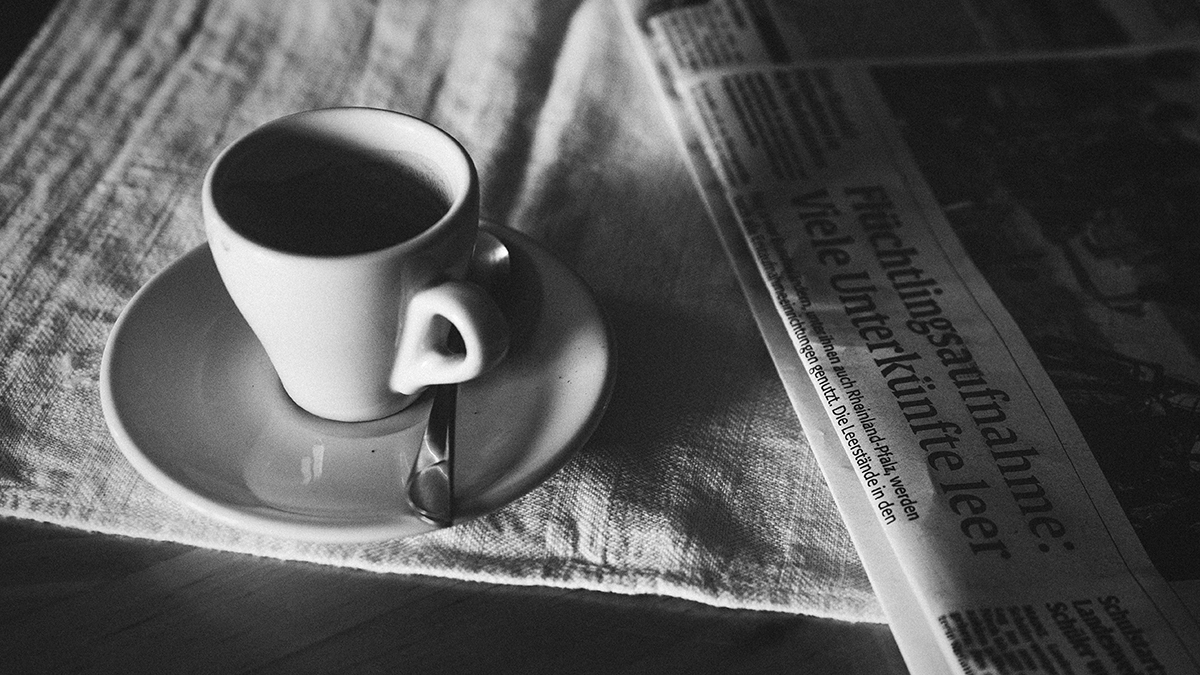 An espresso sits on a table next to a folded up newspaper.