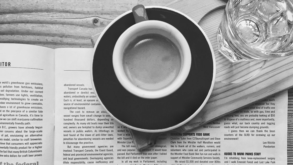 An espresso sits atop a newspaper, seen from above.