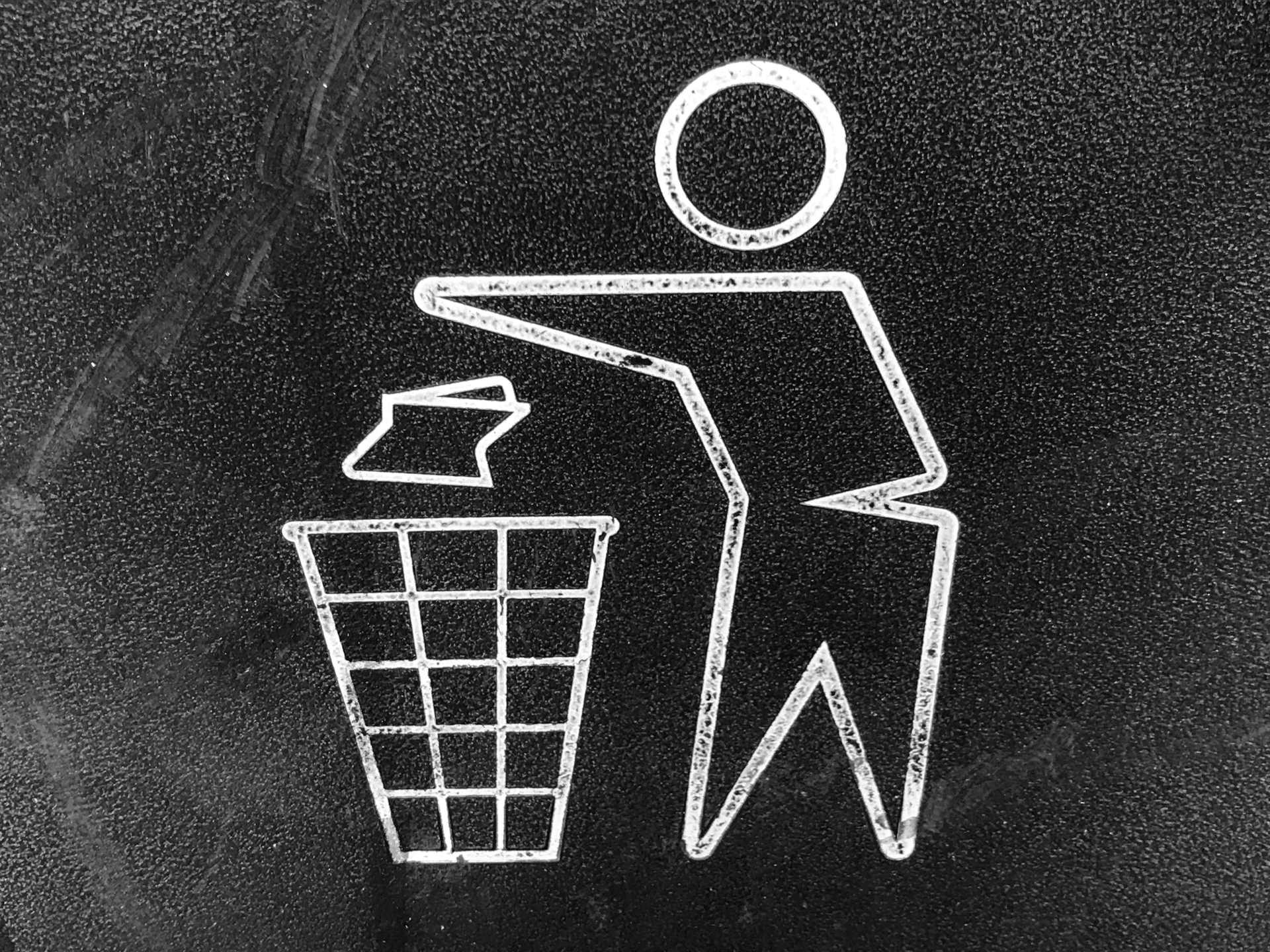 A sign depicting a person throwing trash into a bin.