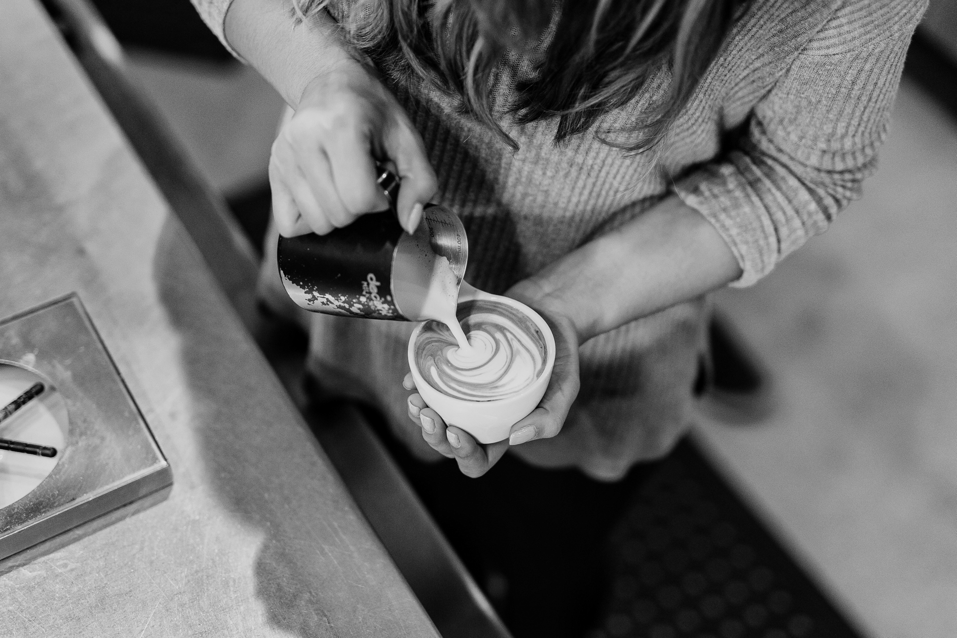 A barista pouring a latte, seen from above