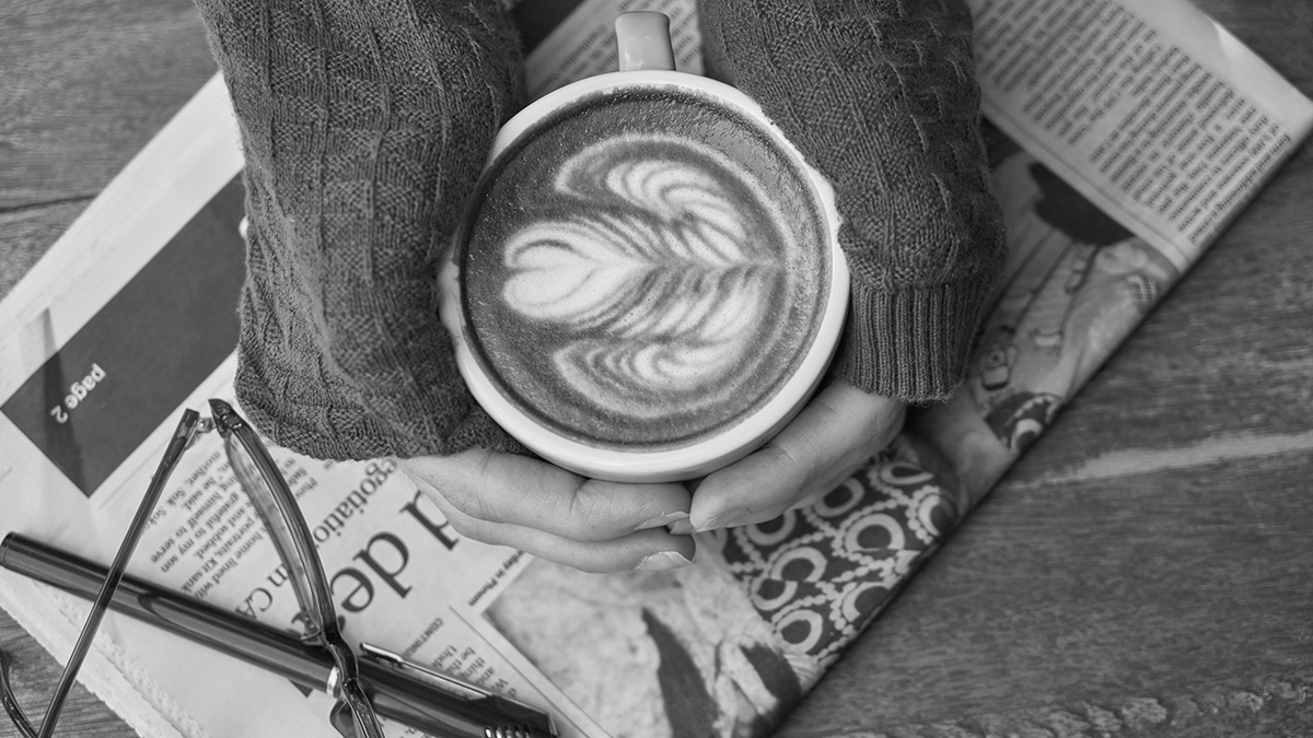 Two hands cupping a latte atop a newspaper, seen from above