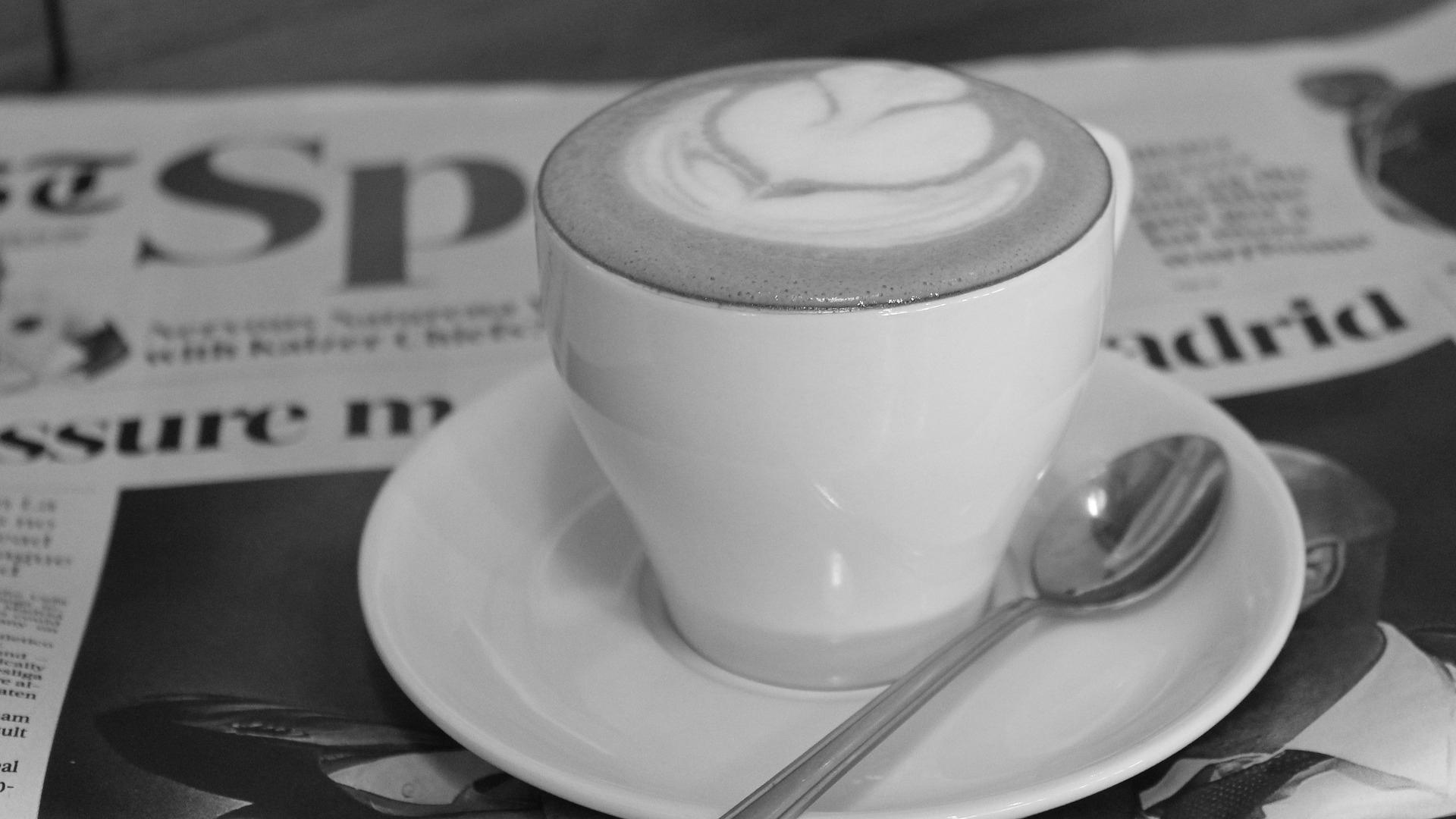 A macchiato with latte art sits atop a newspaper