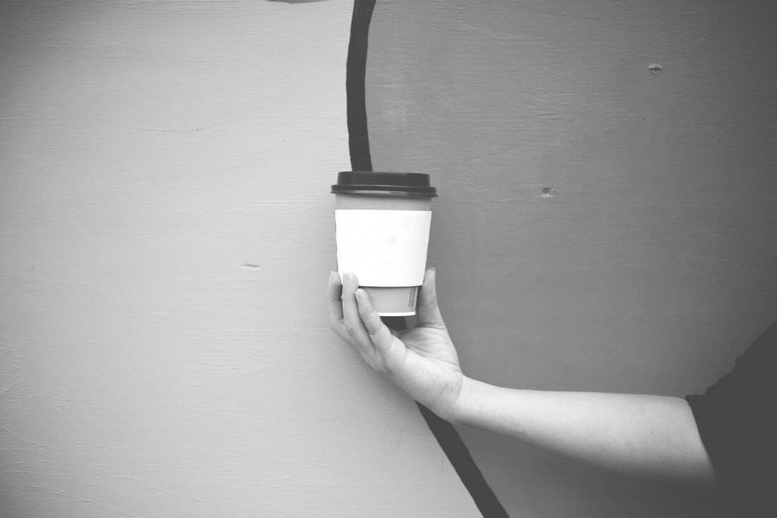 A takeaway coffee cup held up in front of a wall.