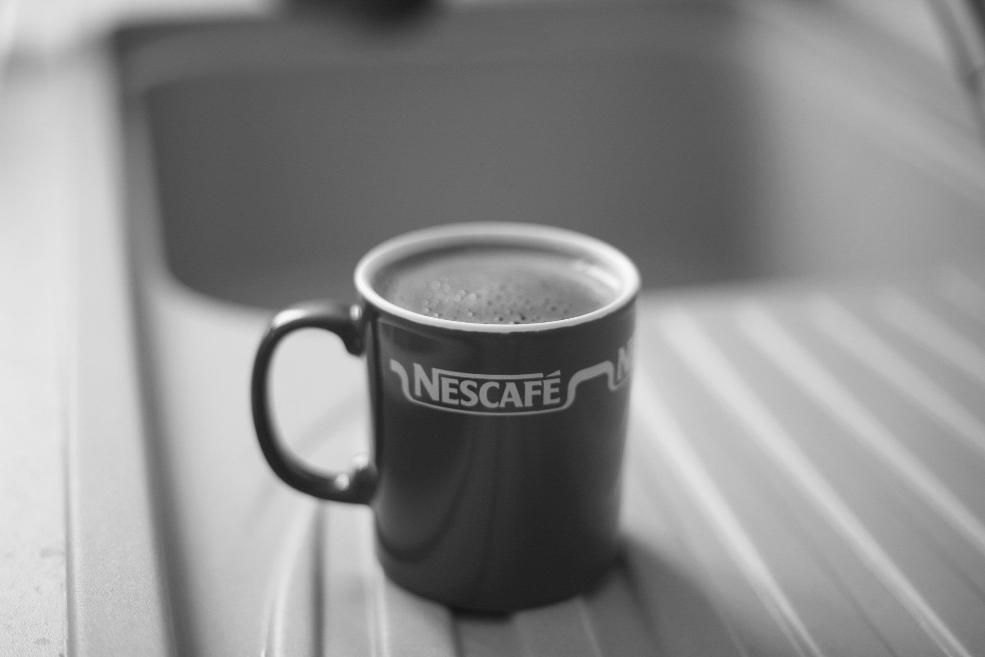 A cup of Nescafe coffee sits beside a sink