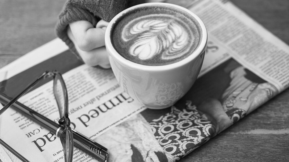 A hand holds a cup with latte art, resting atop a newspaper