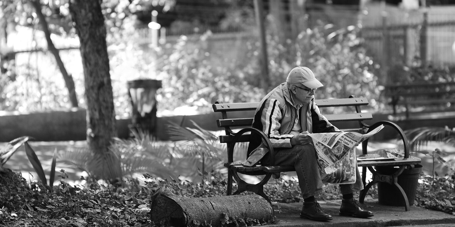 A man sits on a parch bench reading a newspaper