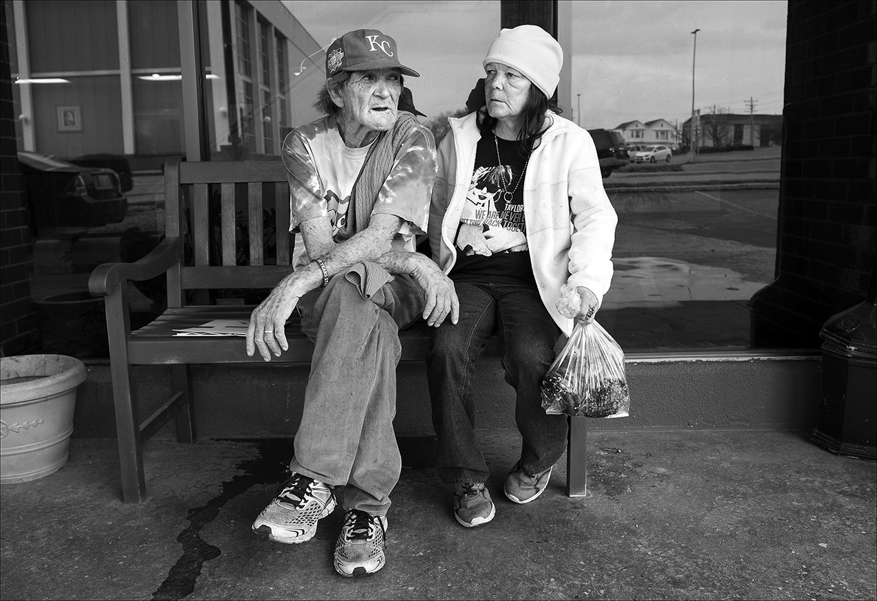 March 2017:  Clarence and Vickie rest on a bench outside the $750-a-month motel. Vickie is carrying a bag of pastries she picked up at the Horizons Soup Kitchen. The couple rely on eating at the soup kitchen Monday through Friday and at Salem Church on Saturdays.