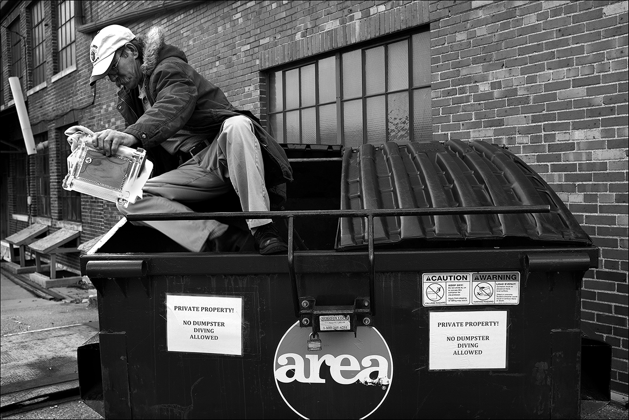 """February 2017:  Wearing nearly new shoes, pants, and parka, Dennis exits a dumpster behind a Maine Street faith-based thrift store where he retrieved the clothes he is wearing a few days earlier. The dumpster is a well-known place to find nearly new name brand clothing and sometimes brand new clothing with the store price tags still on them. Hundreds of perfectly good items like clothing, warm coats, children books, luggage, and other household goods are tossed into the dumpster headed for a landfill on a regular basis.As he was leaving, a thrift store employee steps out to tell him to stay out of the dumpster. """"At first when I started (dumpster diving), I felt like when somebody comes out to tell me, 'Hey, you can't do that,' that's like telling a possum 'get out of my trash.' I'm homeless but I'm not helpless … I'm only poor because of the injury I suffered back in August. Before then, I didn't go into dumpsters. But you have to do what you have to do to make ends meet."""" Dennis questions why a faith-based thrift store throws away clean, usable things people in need could use."""