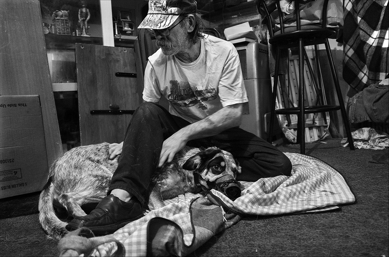 """February 2017:  Dennis tries to calm his dog, Levi, after Levi chewed on a razor and cut his paw. A friend took Levi to a veterinarian at Four Paws in Quincy who treated Levi and provided his needed shots for free. """"I acquired Levi when he was a month old from an Amish family. They gave him to me as a present. He's my companion, he's my guard dog, he's my best friend I don't know what I would do without him. If I have to make a choice between me or my dog eating, my dog's gonna eat.""""  """"There's been times when I was wanting to go ahead and check out. Nobody's gonna miss me. But Levi seems to bring me back to my senses, because I don't know what'll happen with him after I'm gone. He's so loyal that if I was to walk out on a bridge and jump, he'd hit the water first to make sure he caught me. If I had a good friend like Levi, I would never have to question their trust, their friendship, to me. That's one thing about Levi, I don't never have to worry about turning my back, because he's got me 360 degrees."""""""