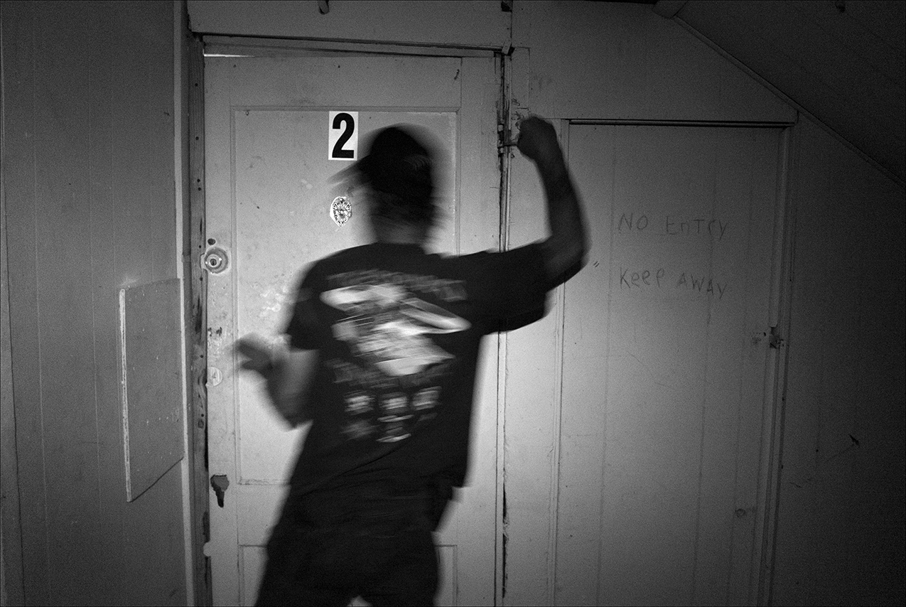 """August 2017:  Late one night, Dennis tries to repair the door to his apartment, but the frame isn't square, which makes it difficult. Dennis is concerned about the possibility of someone breaking into his apartment, so he keeps his guitar in a local pawn shop, where it will be safely stored. """"The traffic has slowed down. Before it was like they were all standing in line waiting to use the bathroom to shoot up. We'll always have a dope dealer, dope people and cops chasing people through one door and out the other. That's why I got a dog, to keep people away from my door."""""""