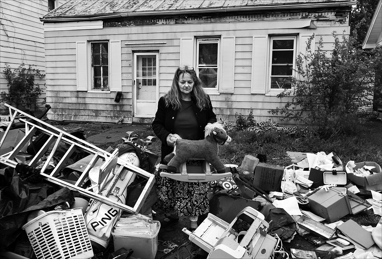 April 2017:  Elizabeth is suddenly homeless. After working sleepless through the night, Elizabeth rummages through her belongings the following Saturday morning. She says she lost her home of 20 years because of about $2,000 in unpaid property taxes. She says she tried to fight the takeover in the courts, but when she lost, movers for the new owners arrived with sheriff's deputies and set everything she owned out in the rain. She says trying to save her home from being taken out from underneath her, consumed her life night and day since July 24, 2016, when she first saw the legal notice in the newspaper. Assuming her mortgage lender had paid the 2012 property taxes, Elizabeth says she was on a sabbatical from work to take care of her 84 year-old-mother who had a broken back when she discovered in a newspaper her name and that they were filing to take her property.