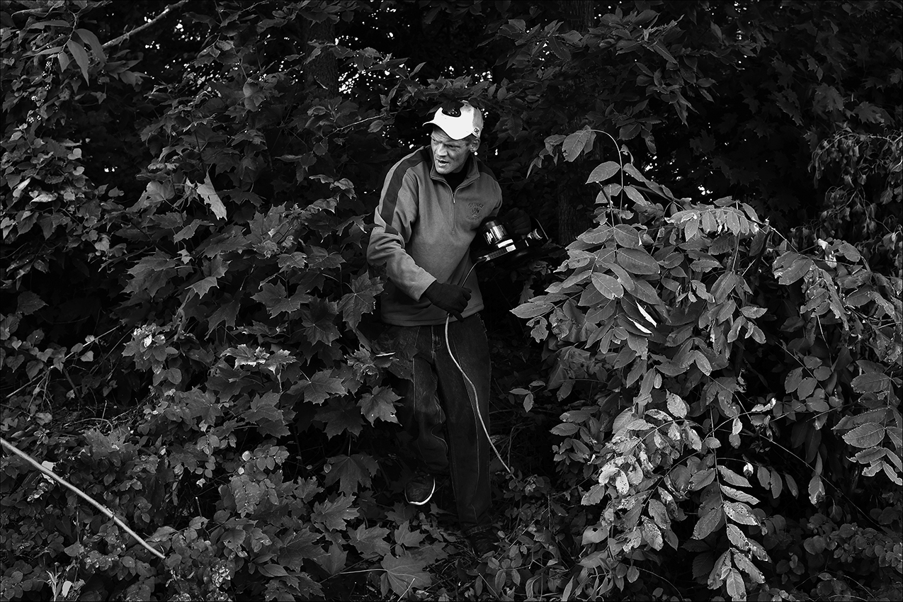 July 2016:  Wearing a long sleeve coat in the heat of the day to protect against poison ivy, James clears brush for someone he met recently. James says he offers to help people with odd jobs. He says he doesn't ask to be paid anything, but usually receives tips.