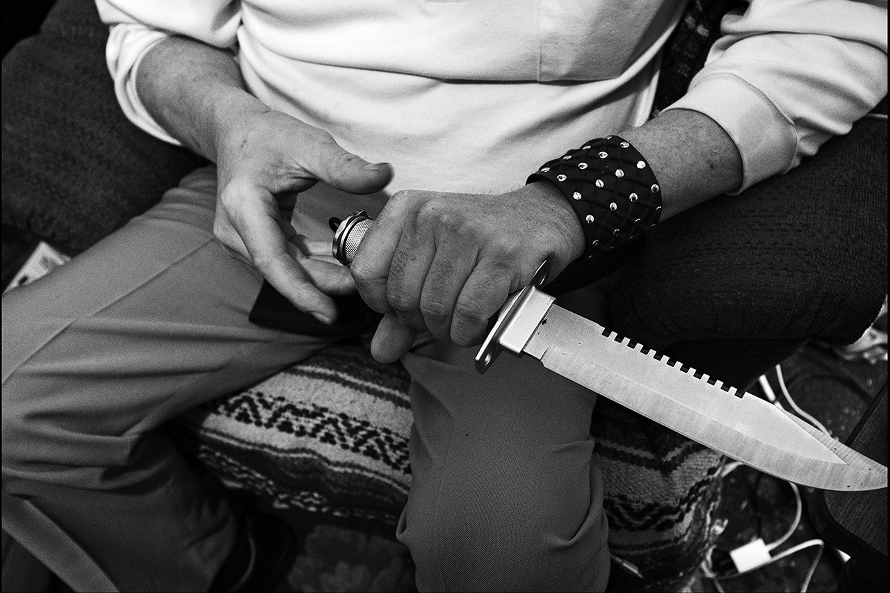 """March 2017:  Dressed in his Sunday church clothes, Joseph displays a knife he uses for protection. """"It's a shame I have to carry all this hardware around to protect myself,"""" he says. """"It goes back to not having enough money for just simple survival. It's trying to have enough to eat, making sure that you don't starve to death out here in the streets. It gets down to the point where people break into your house and take your food, your medicine. My next door neighbor, Pat was killed,"""" Joseph said. """"I guess they wanted drugs or something, but they had broken every bone in his face, every rib but three, and broke his arm in two places. He passed away in the hospital several days later."""""""
