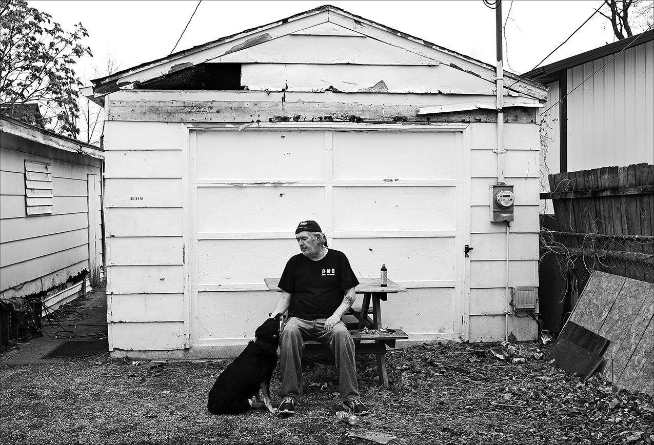 """February 2017:  Joseph sits with his dog outside of his converted garage apartment on the north side of town. The apartment is tiny, with mice scurrying around inside during the day. Joseph doesn't feel safe, but it's what he can afford. Joseph used to be a furniture mover but became disabled when his knee blew out.  """"After the knee went, there wasn't a whole lot I could do,"""" Joseph said. """"I did go to culinary arts school. I got two degrees in culinary arts, but I can't stand at a grill for eight hours any more to, you know, even to do shift cooking. After I was hurt, I couldn't work a regular job.""""  Joseph now volunteers his time at various organizations.  """"I worked with a lady here in town,"""" Joseph said. """"She worked the Jefferson Center on the north side. She gave me a job working with kids, and that seemed like something I was good at. Kids and animals love me. I worked there probably 14 years. It even got to the point where she talked me into playing Santa Claus a couple of years."""""""