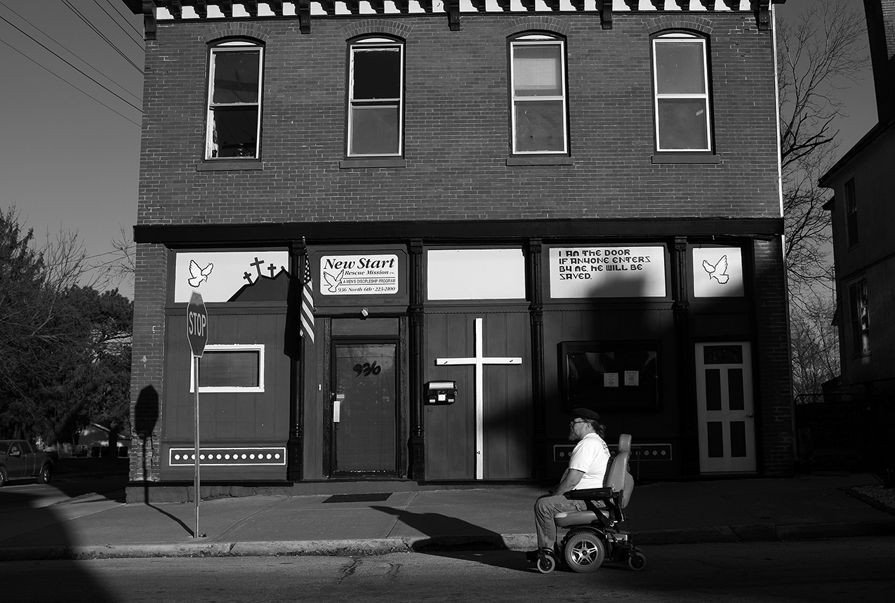 """February 2017:  Mark maneuvers his wheelchair on the street to avoid sidewalks in disrepair. """"I'm currently in a handicap accessible apartment which is ideal for my wheelchair and me. But, I also need to get to meetings, to get to the soup kitchen, and I need to get to the pantries, and that requires me to go out with my chair, which in itself has been an issue. I've had to have two complete sets of tires on my wheelchair replaced.The chair is just like a car to me. It cost me just about what a car would cost except for I don't have gas I got electricity. That in itself is 80 to 120 dollars a month.""""  Mark says maneuvering some of the Quincy sidewalks isn't ideal. """"They got potholes on the sidewalks that if you hit one of them with these tires it's gonna break 'em. I can't get around without causing damage to my chair. Without this chair, I couldn't do none of what I do.""""  Mark talks about wheelchair inaccessibility issues. """"It's demeaning, you know? I'm close to uptown and I like to shop. I don't necessarily like to buy things but I like to keep track of trends. I can't even get in the store to see what they got. There's a lot of buildings I would like to get into but can't."""""""