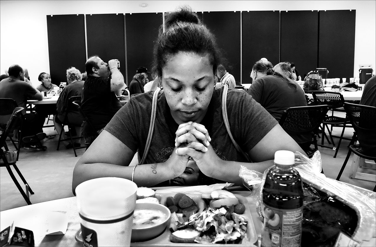 """September 2016:  Nakia says grace before eating lunch at the Horizons Soup Kitchen and Food Pantry in Quincy. Nakia says she is on the verge of homelessness. """"I work at two different fast food jobs, and I'm a hard worker and a fast learner, but sometimes I'm only given five to nine hours a week between the two jobs. My babies depend on me,"""" she said.  About a year later, after experiencing some financial stability, Nakia says her children were taken away by DCFS. She says she is woking towards getting her children back."""