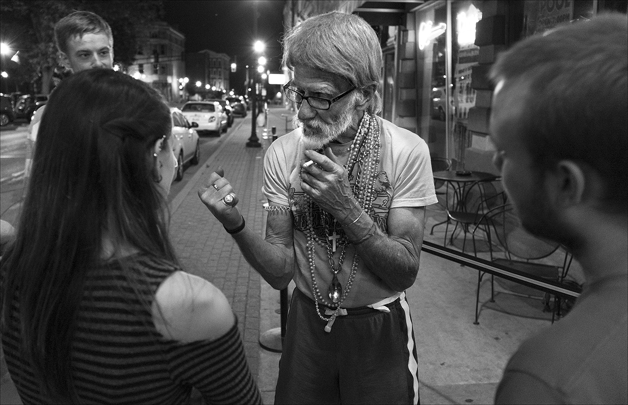 May 2017:  Walter stops to talk with a group of college students outside a bar across from Washington Park. They are intrigued by his stories.