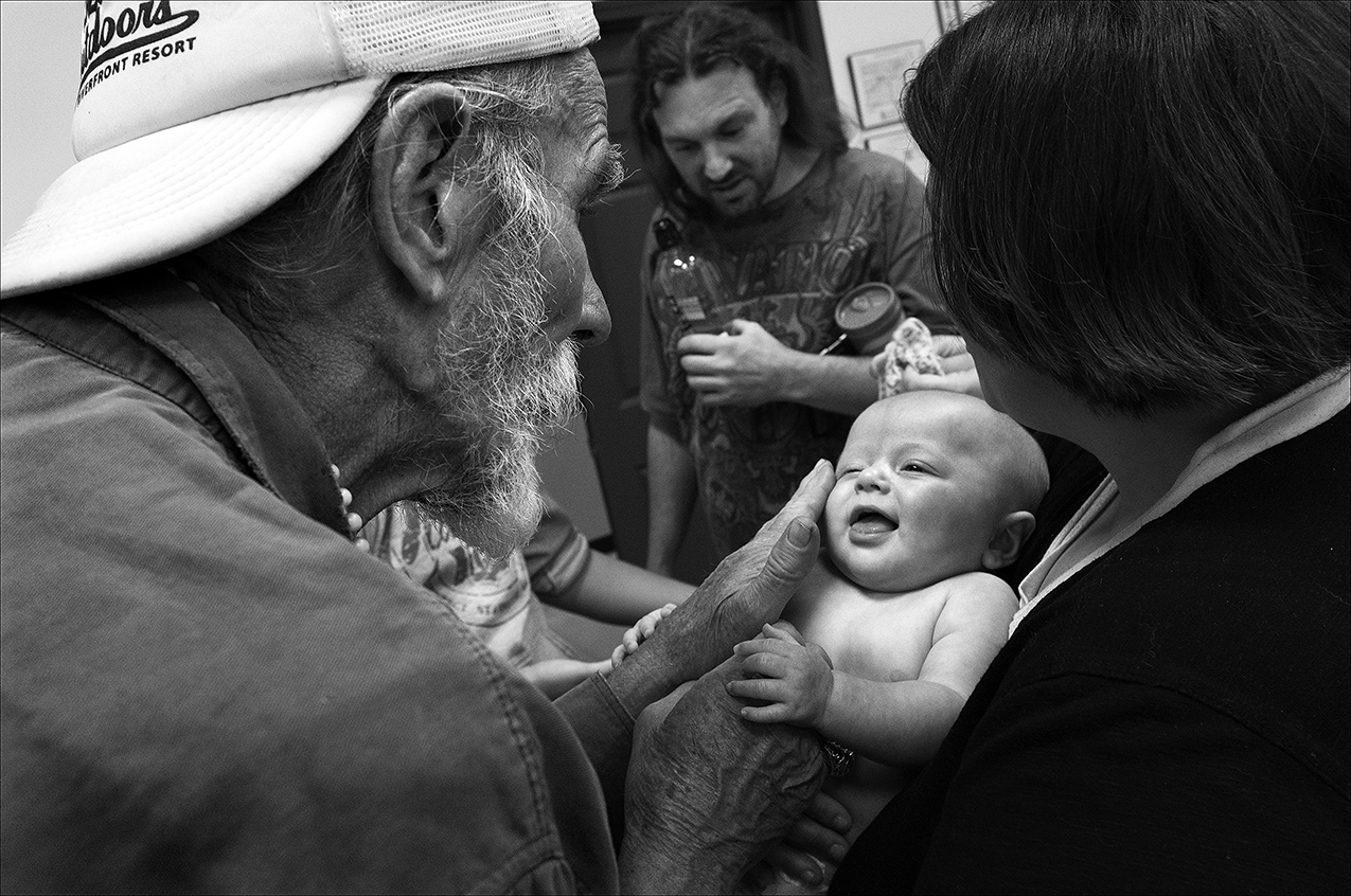 May 2017:  While waiting in line to eat lunch, Walter plays with an infant, an interaction that raises his spirits after being homeless for five days.