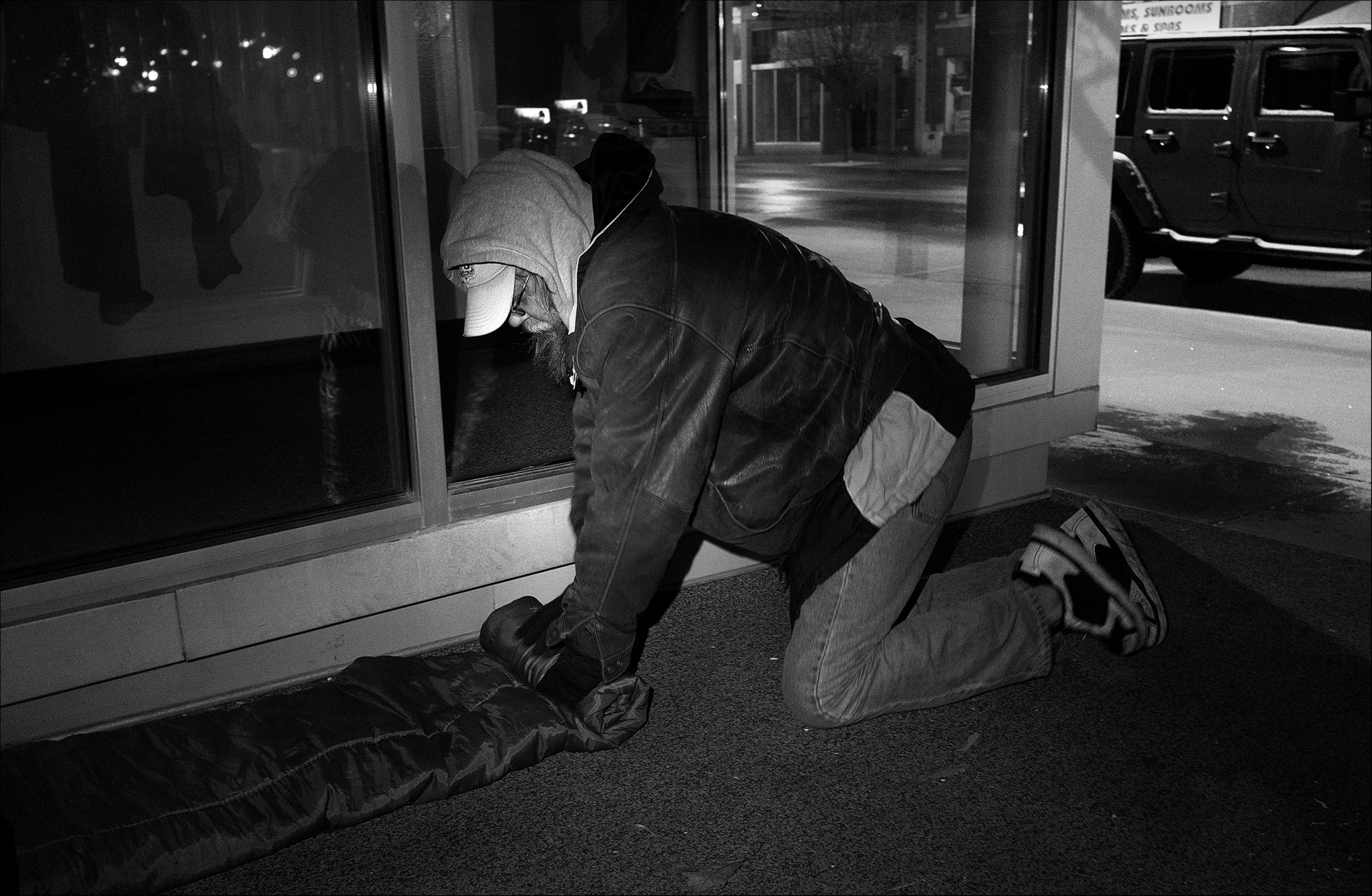 """March 2017:  Rising early on a freezing morning to avoid any possible complains, Wes rolls up his sleeping bag where he often sleeps on Maine Street in Quincy. """"The first night I was actually homeless, I'm sitting here carrying around, at the time, everything I own, which is about three big black trash bags. And I'm sitting here going, oh my God. I'm actually gonna have to sleep out without a tent, without a sleeping bag. How in the hell am I going to do this? I ran onto a dude and he and I talked a little bit, and we kinda got along. This is the middle of February, it turned out cold that night and he and I were like, I mean, you talk about a couple of dudes not wanting to, but then yet still, I mean, if we hadn't snuggled up to each other we probably be both dead. I mean it got below freezing that night."""""""