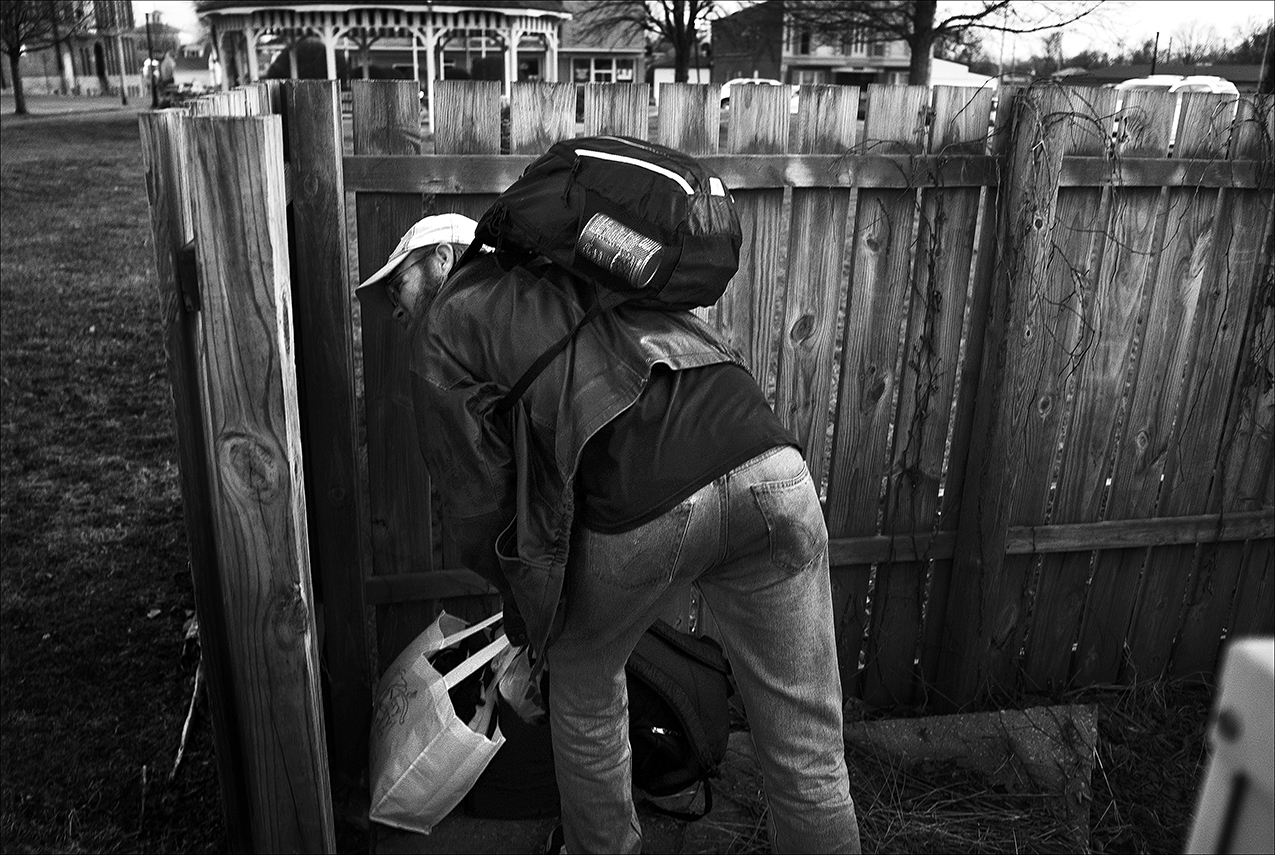 """February 2017:  Wes stashes his bags at a location near a church, but a few hours later, his bags are found by a maintenance worker, and he is asked to no longer use that place to hide his belongings.  """"I've got two whole sacks, I've got a backpack, and I got another backpack that keeps my sleeping bag in it so I'm basically carrying three bags, which at any given time probably would weigh at least 50 pounds, which is okay, I gotta work out somehow. But, like, if I need to go in a store, I can't take that in with me. If I need to go in and get some food, or whatever, I can't so I need to try and find places around town where I can stash my bags for a little while anyways, and it always makes me nervous. I will do it and it's been okay, all right, except for a time or two. I've actually had my stuff stolen in the past. So I'm very leery. I want to keep it with me but you can't and you can't just stick it around the corner of the store and walk in. It's just really difficult.""""  """"I had my bag stolen one time - it had my insulin and syringes in it. I had to be admitted to the hospital for two weeks."""" I'm gonna tell a story. I stashed my stuff to go to the store because I can't carry it in with me. This person noticed it and immediately ... and she's supposedly Christian - she immediately was like going, is that your stuff? I'd been gone a half an hour and that's all it takes. She said you can't put your stuff in there. We don't allow people to sleep in there. And I'm like, ma'am, I have never slept in there. She was like, okay, all right. Just don't ever do it again, blah blah blah. I don't know, that was really Christian like, wasn't it?"""" In Springfield, Missouri, they used to have a day shelter with lockers. It didn't cost you anything. You could wash your clothes in there. Didn't cost you anything. You had to wait in line, and it wasn't the best in the world but still, you could store your extra stuff there."""""""