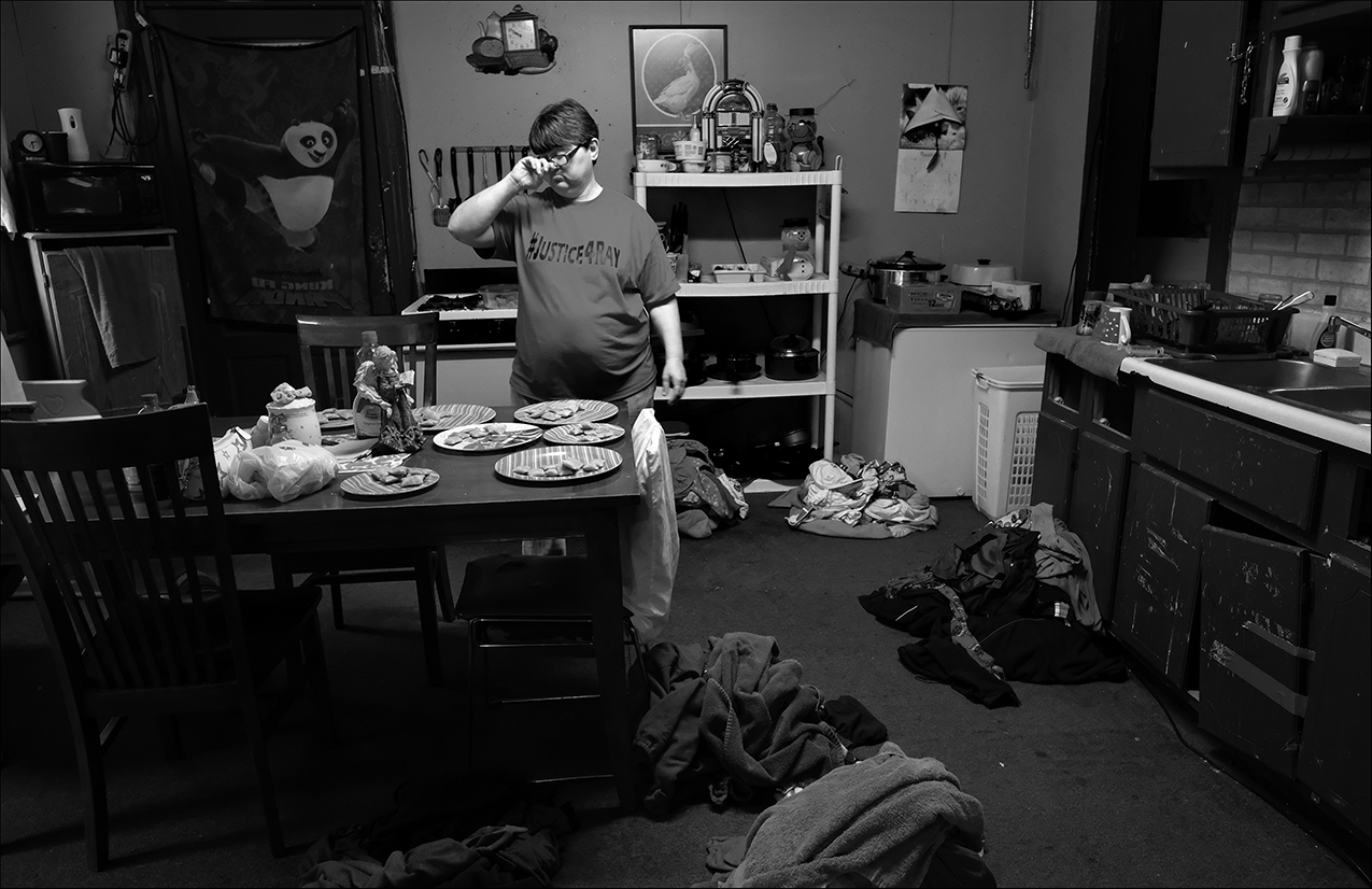 "March 2017:  Wendy pauses a moment to gather her thoughts while preparing laundry and supper for the family of eight. Despite health problems of her own, she has had to assume all household chores, as Chris is debilitated by cancer.  ""Wendy's been there beside me the whole time I've had cancer, and she hasn't let me down. I thank Wendy for every day she's been there beside me. She gets out here and she knows I can't do it, she gets out here, she cuts the grass, she helps take care of the house, takes care of the kids and the laundry. She does a lot and if anybody calls and needs a ride somewhere she gets up and she goes and does it. I don't care if it's all day or all night long, she'll do it. She'll do anything for anybody. She don't get much rest. I try to help as much as I can, but she does a lot,"" Chris said."