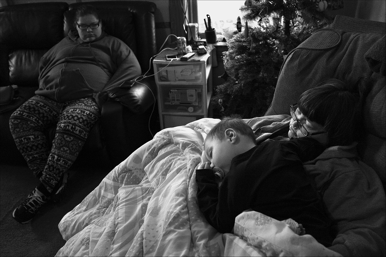 "December 2017:  Wendy, Courtney, and Carson, wait in the cold without heat for repairs to the gas lines in the basement to be completed. Outside it's below freezing. Wendy and Chris say the landlord told them they would have to move out of the apartment earlier that day when gas leaks were discovered. But with nowhere to go, they panicked and called several social service agencies for help. Chris says they were told there was no help available. Their duplex neighbor, confined to a wheelchair, said she was told the same thing, that she would have to find a place to go. The neighbor and Wendy and Chris stated after the neighbor threatened to sue, the landlord returned and promised repairs would be made by that evening.  ""When we smelled the gas, my daughter Googled it and it come to say that it smells like rotten eggs or anything. Then you've got a gas leak,"" Wendy said. ""So, we called the fire department and they came out. Well, the landlord come in and tells both sides we had to move out and all because of the gas leak. Then come to find out, they went downstairs and looked and they found one, two, three, four leaks in the basement around the hot water tank and the furnace. The landlord told us we had to pack and move. We had nowhere to go. I was worried about Courtney being pregnant and Chris has cancer and then I have my cousin Kristy that's got one foot, problems with my health problems of my heart and everything,"" Wendy said. ""We had four little kids in the home. My cousin, Jeffrey, I mean my nephew Jeffrey lived with us. We had nowhere to go because we had no family. I didn't have nowhere for the dog to go either.  ""I was upset. I cried. Courtney was crying, I had to calm her down because of the baby. It was just hard,"" Wendy said."