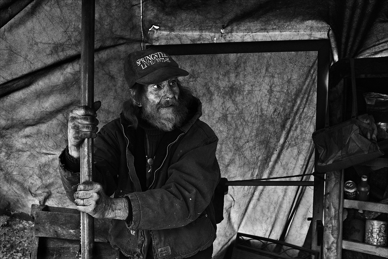"""December 2017:  Walter holds the center pole of his makeshift shelter so it doesn't blow away on a windy afternoon. He's covered in soot from the open fire he uses for warmth and to cook. He wonders if he brought his recent troubles on himself because of """"living in sin"""" with his girlfriends of 24 years.  """"I walked away from my teaching and got in trouble by not doing what the Word of the Lord says. You're not supposed to live with a women unless you're married, that's what the Bible says. Paul said 'marry or burn' and that means either get married or go to Hell. And if you don't believe in Heaven and Hell, I feel sorry for you Enough said on that subject."""""""