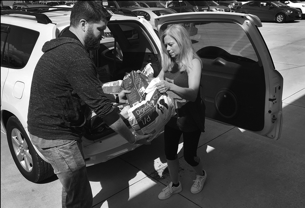 Mary Welk, right, with K-9 Connection delivers an SUV full of dog and cat food and supplies to Horizons Soup Kitchen and Food Pantry Wednesday, Sept. 12, 2018. Dain Duffy of Horizons helps unload the items. The Quincy Illinois Poverty Project reached out to K-9 Connection after seeing homeless people in Quincy, struggling to feed their pets. Welk and others in the rescue organization, stepped in to offer assistance, which led to them partnering with Horizons to provide the pet food at the food pantry for those in need.