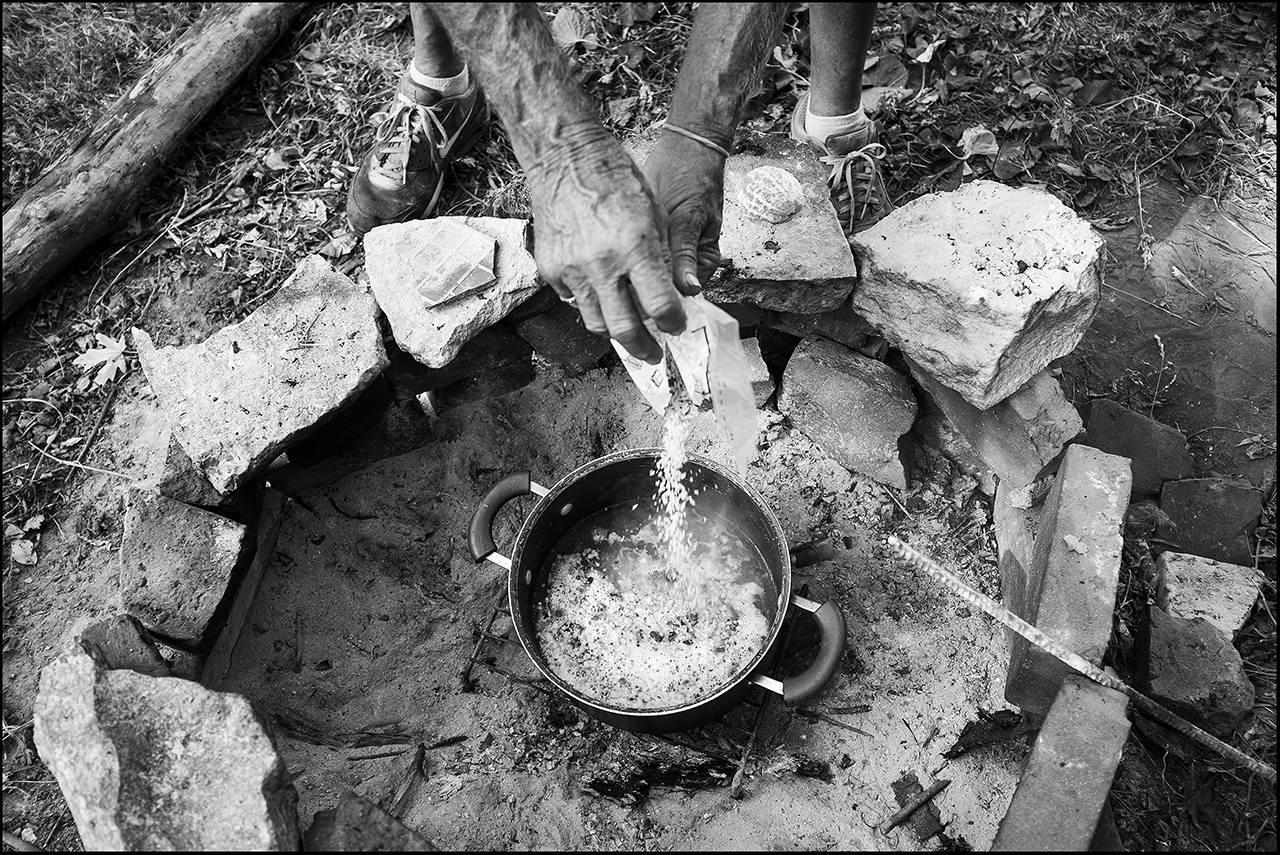 July 2017:  Walter, 74, cooks his dinner of rice on an open fire in the yard of the house he is renting for $400 a month. The landlord had promised the meter box housing would be replaced upon move in, but that didn't take place. Walter, living without electricity, or gas, must cook on an open fire outdoors. This situation lasted through the entire winter.
