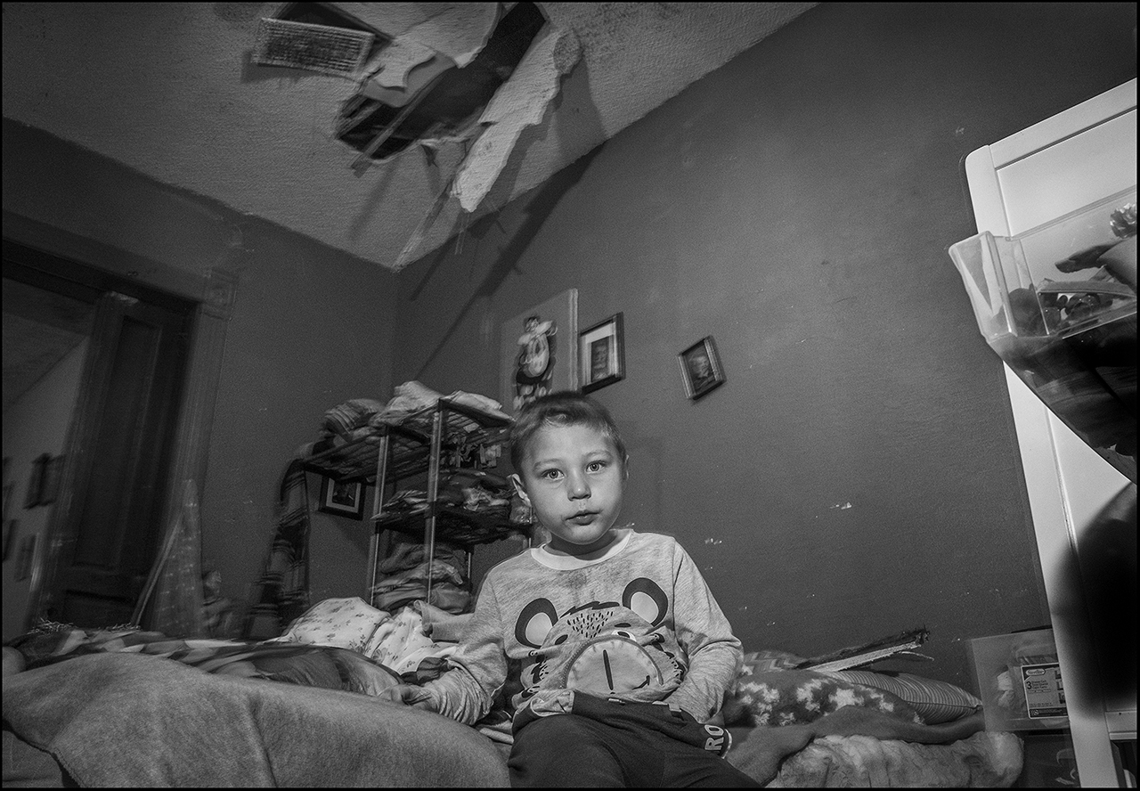 """November 2018:  Carson sits on the bed where nails and splintered wood crashed down upon the spot he and his grandmother sleep, after his mother fell through the ceiling, above. Wendy S. said she's been asking her landlord to repair the dangerous upstairs floor for 6 months, but he didn't do the repairs and her daughter fell through the ceiling, escaping serious injury, or death. """"It's got me to where I'm scared, I'm frightened, I'm overwhelmed. I'm scared for my kids. Its not safe anymore. So, I just need to be done. My anxiety is through the roof. It's through the roof. The room looks like it's just like somebody dropped a bombshell and the whole thing came down. I can't imagine if I was sleeping and waking up to that hitting you, and ... No, I just thank God that it wasn't at night."""