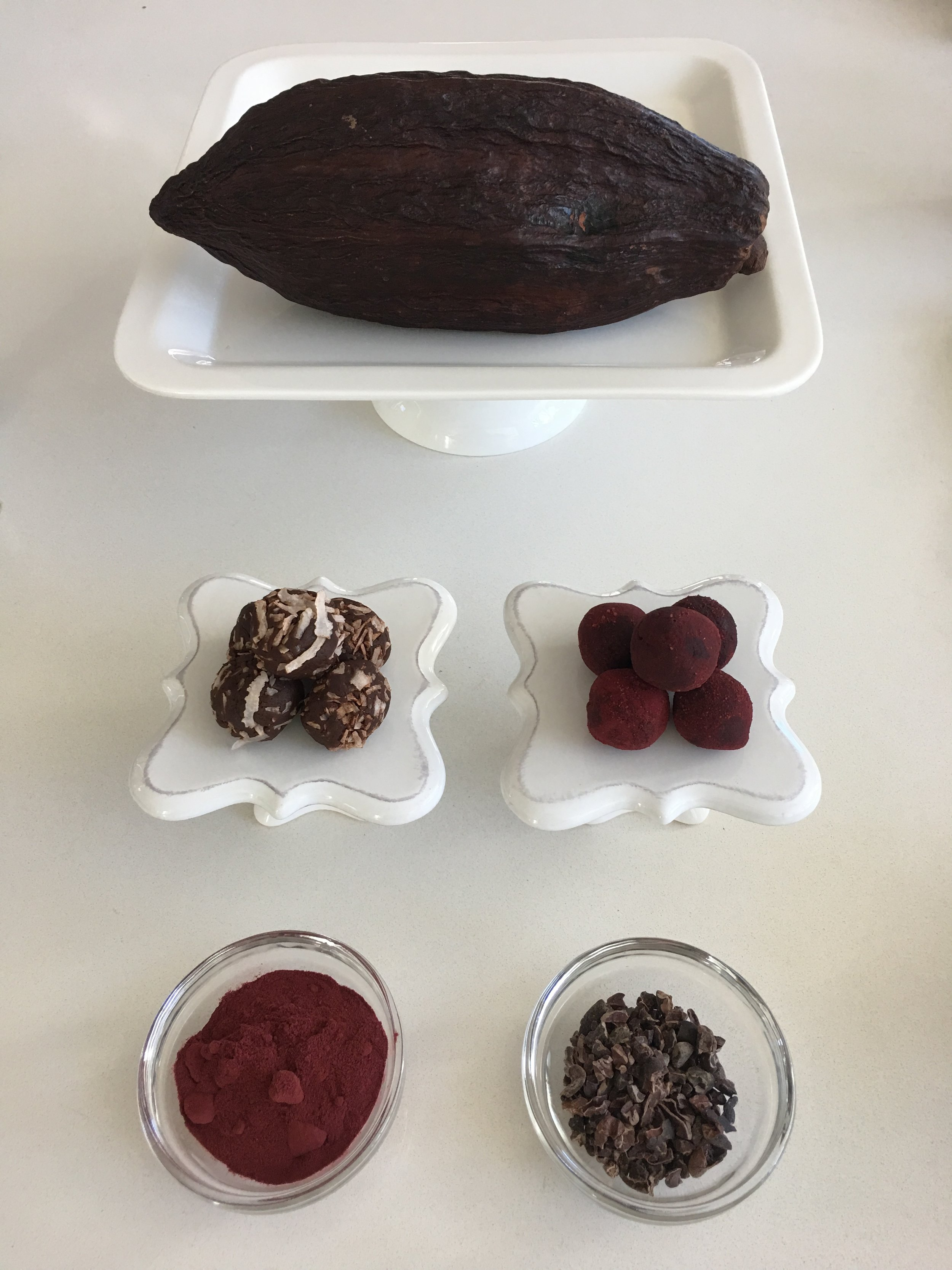 CACAO POD ( top ), Cacao Protein Bites rolled in shredded coconut and beet root powder ( middle ), Beet root powder, Raw cacao nibs ( bottom )