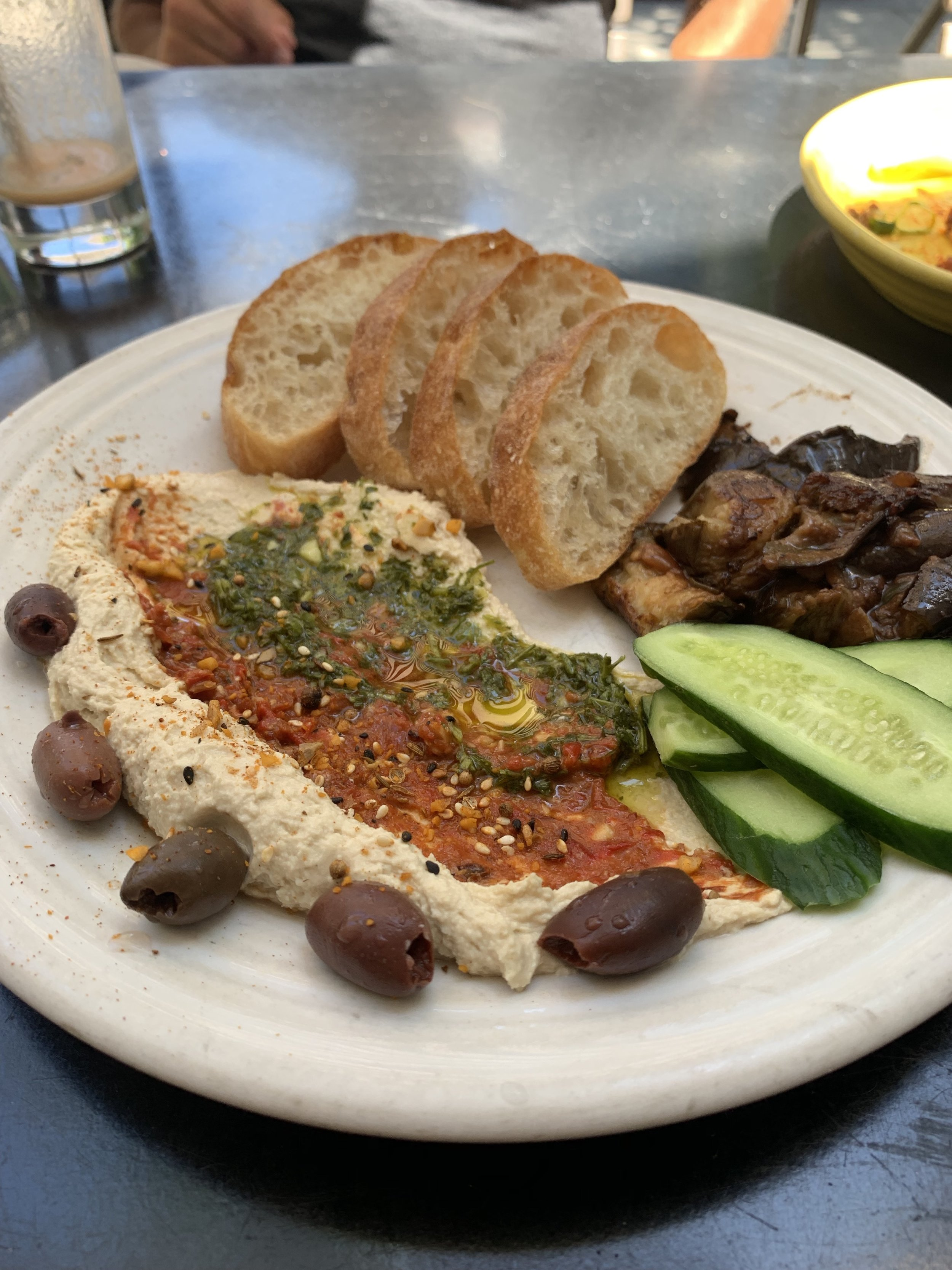 KARMIC chickpea hummus plate could be a meal: red pepper walnut muhummara, cilantro zhoug, dukkah, sumac, olives, veggies for dipping and ciabatta