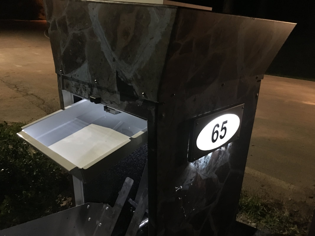 this unit, pictured at night, includes the added mailbox accessory. mail and parcels can be retrieved from the rear and all deliveries are made to the front of the mailbox sentinel. parcels go in the bottom and mail goes in the top keeping deliveries separate and secure.